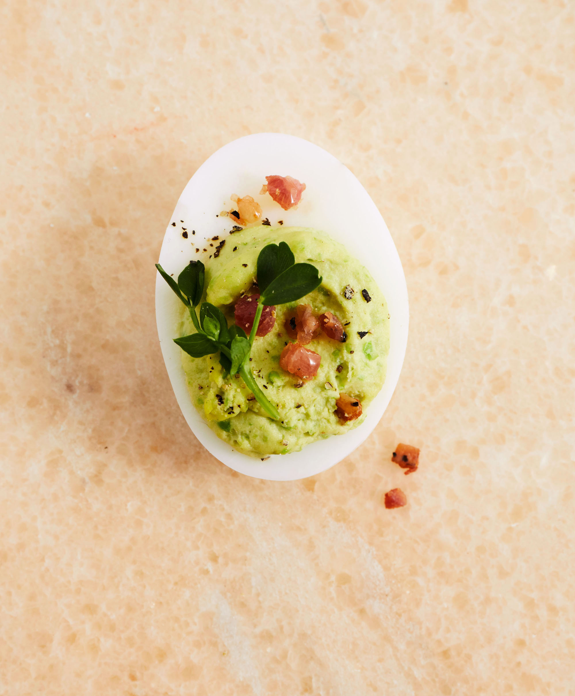 deviled eggs with ham and peas topped with fresh pea shoots