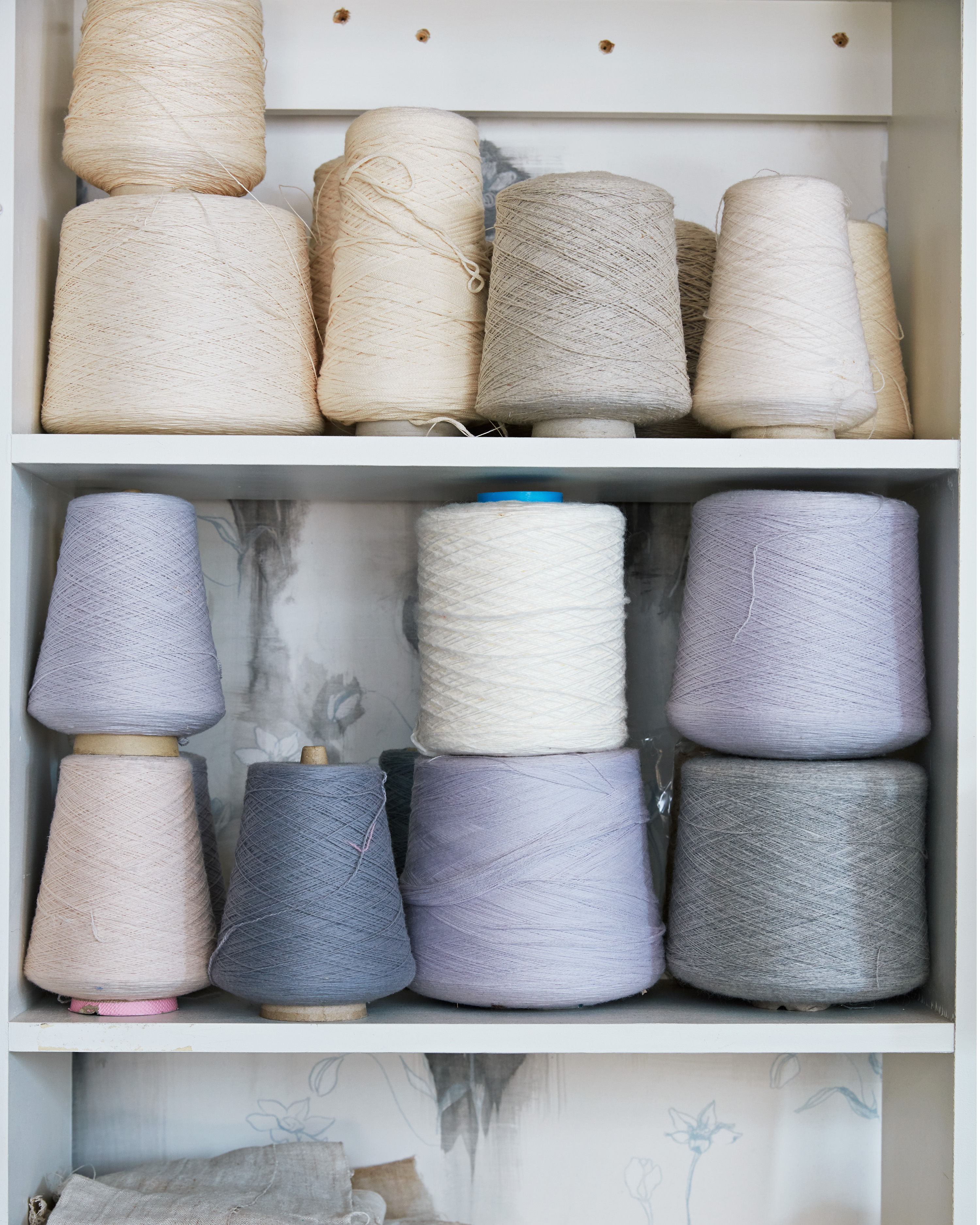 assorted spools of thread on white shelves