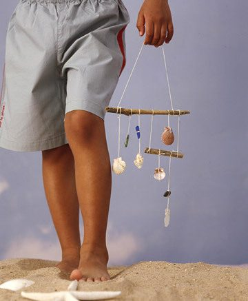 person holding shell wind chimes