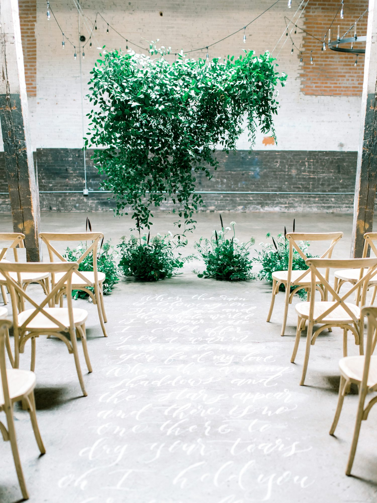 ceremony aisle with song lyrics and greenery