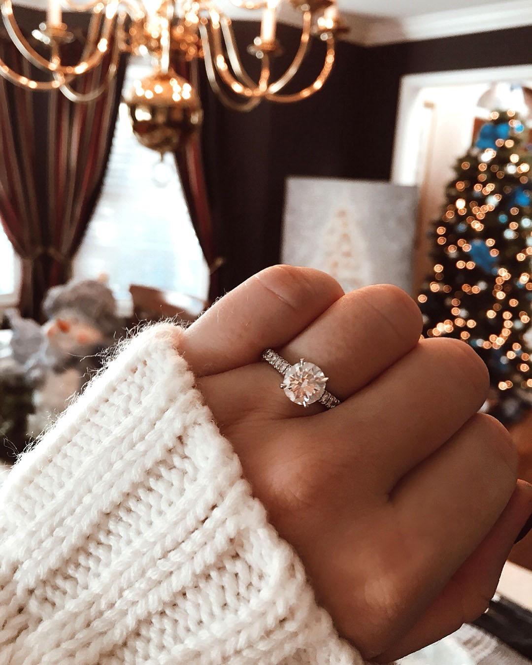 engagement ring selfie in front of christmas tree