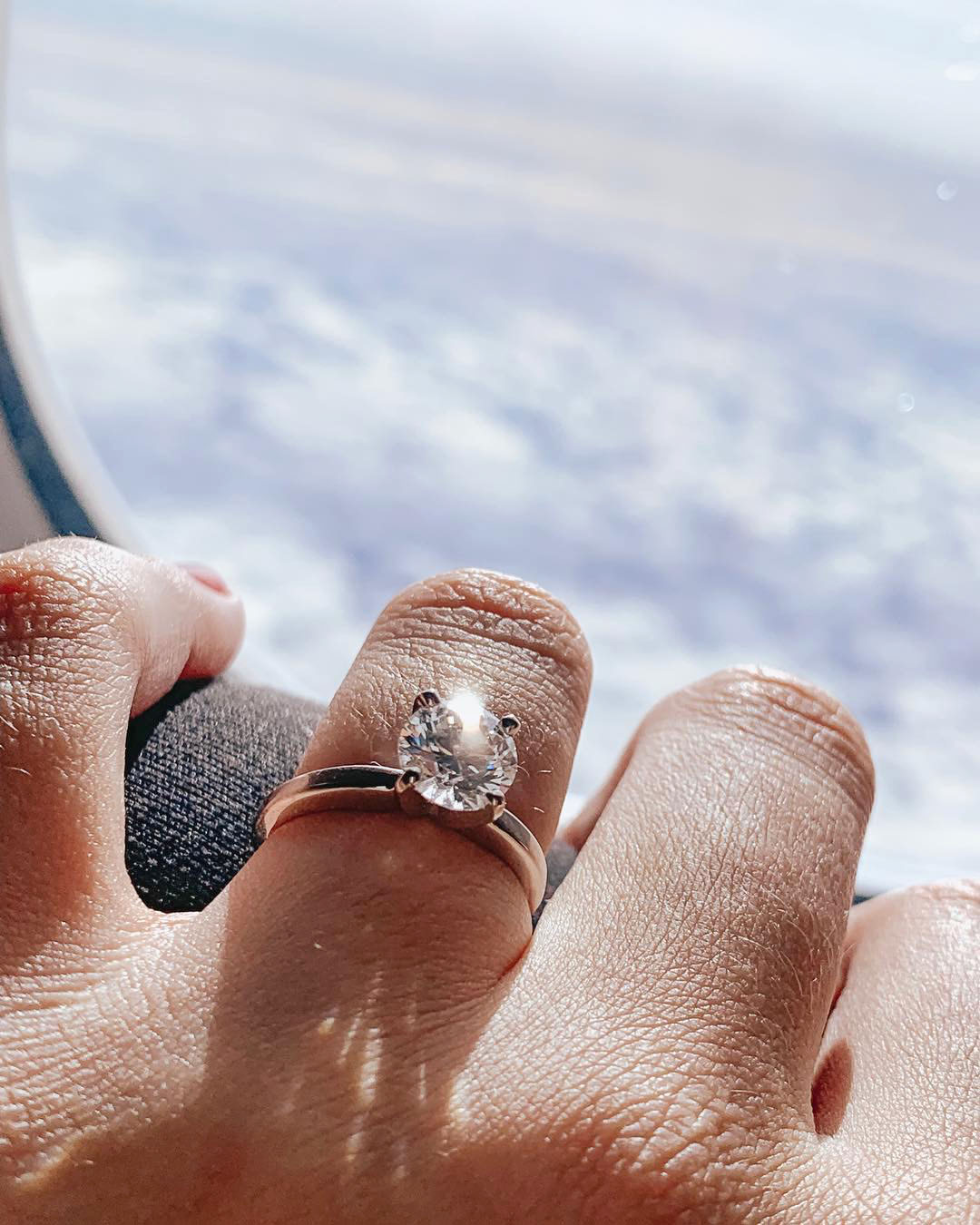 engagement ring selfie airplane window view of clouds