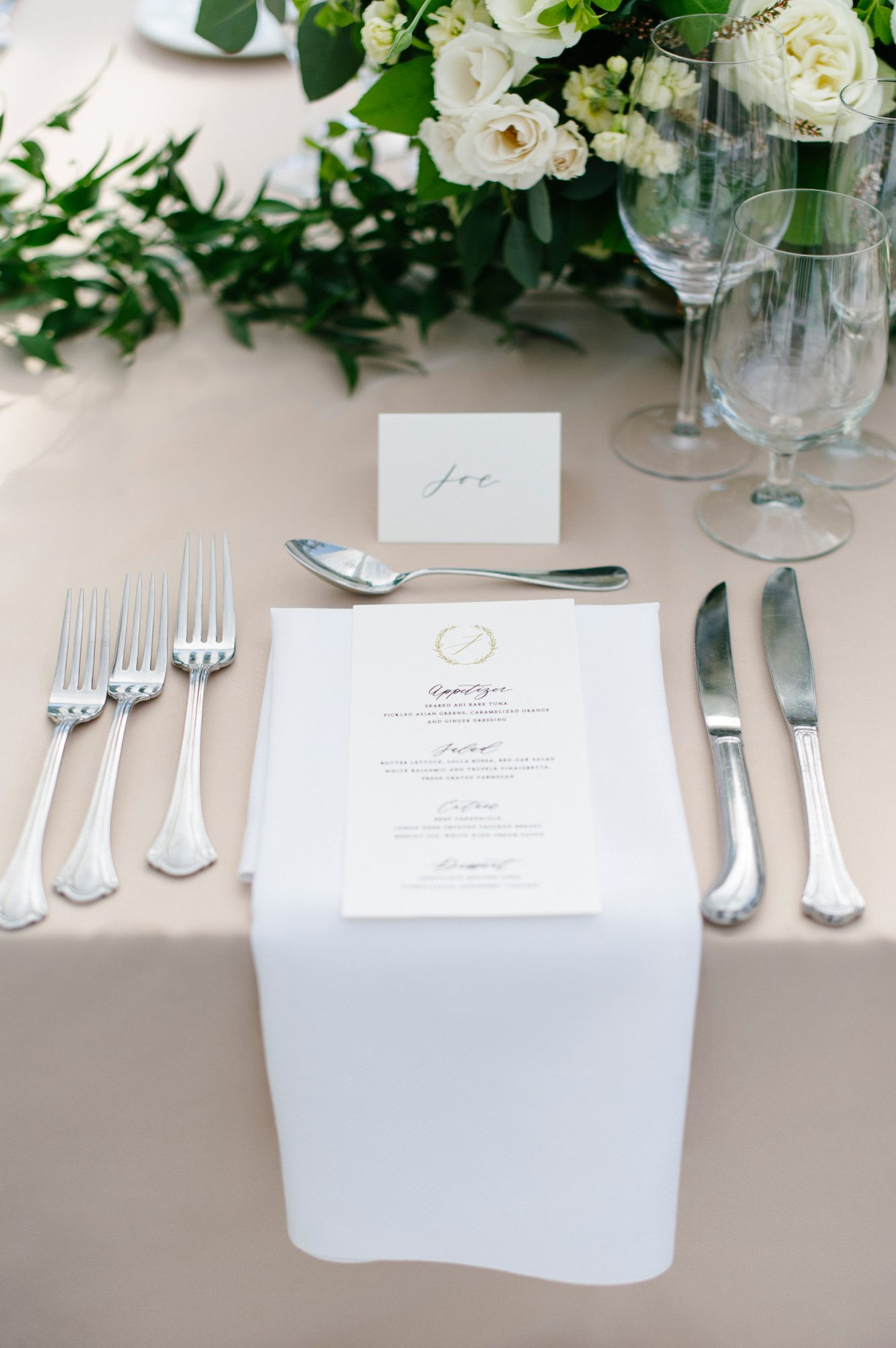 white and silver place setting with monogramed menu
