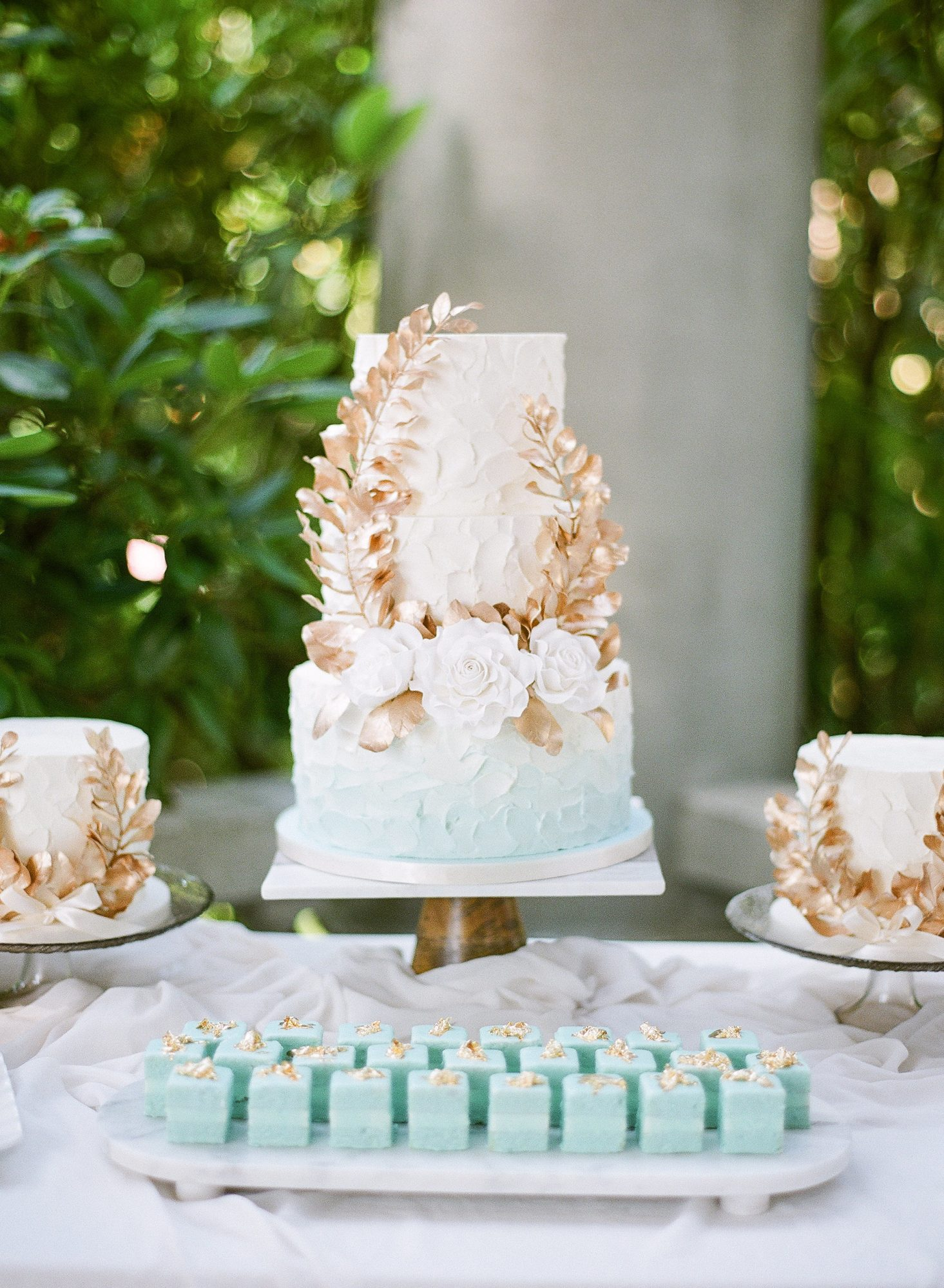 The centerpiece on this couple's dessert table was an aqua-tinged ombré buttercream cake by The Cake & The Giraffe.