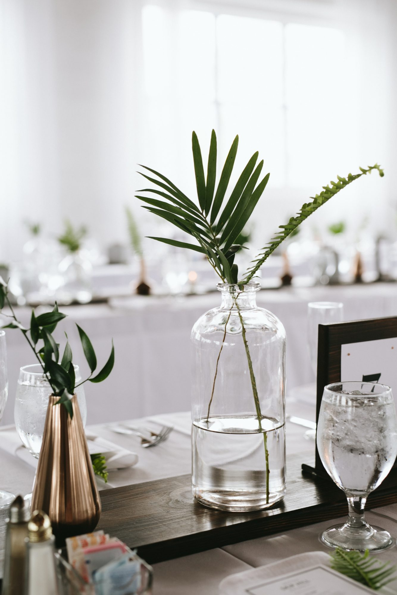 modern wedding centerpiece with copper and glass vessels