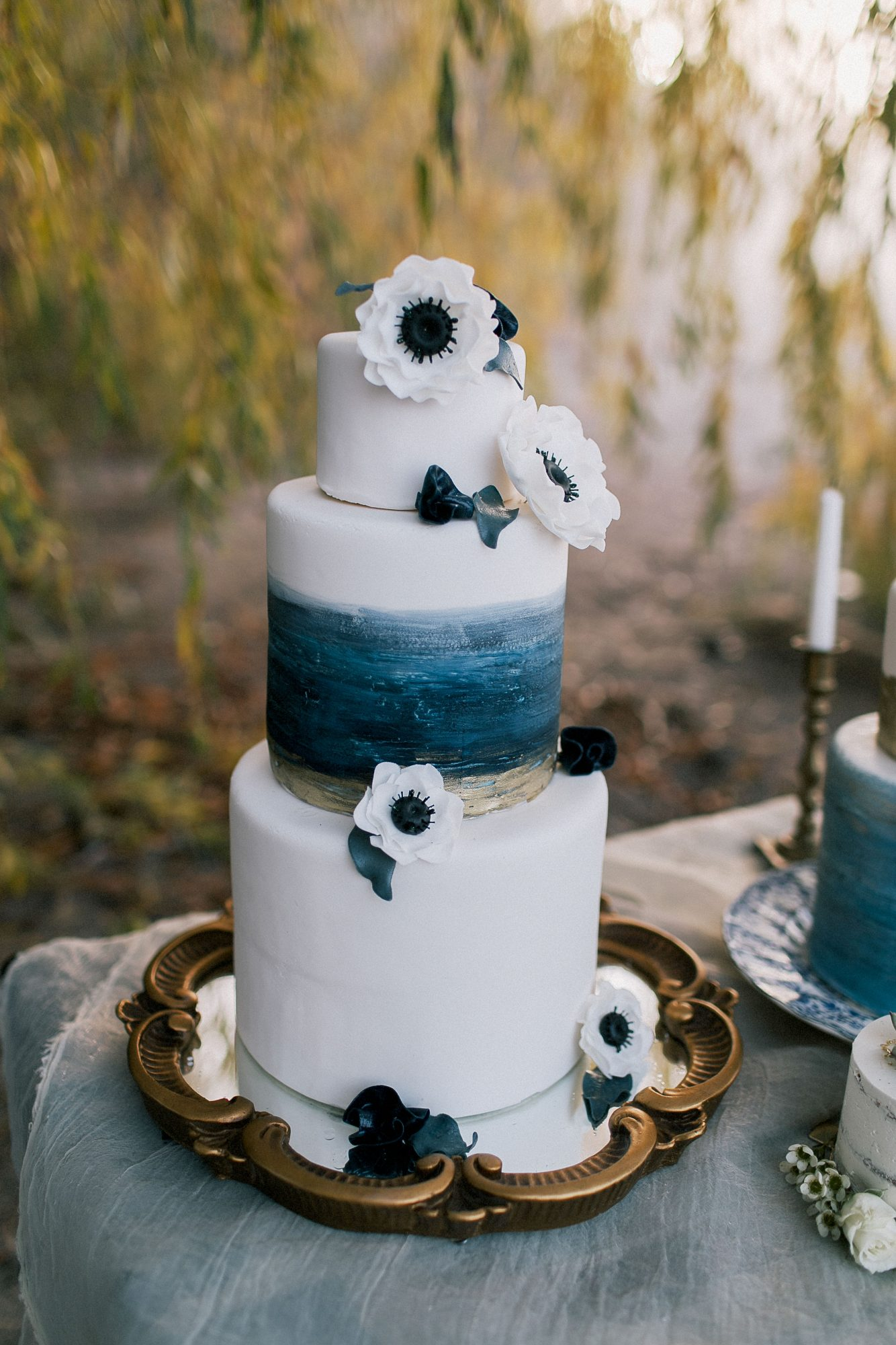 The Cake Baker scattered sugar anemones on this white, blue, and gold dessert.