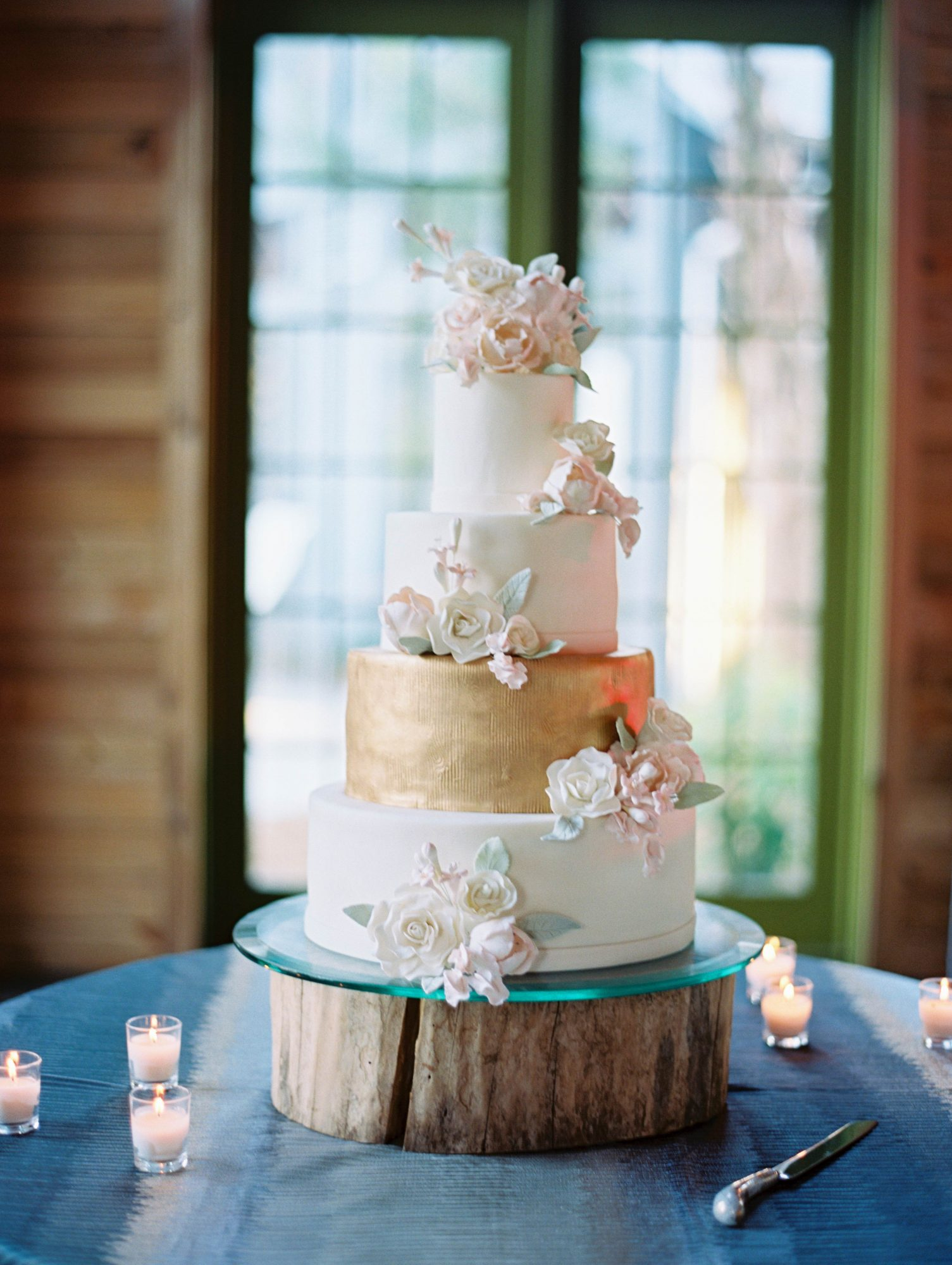 Confections on the Coast finished this four-tiered cake off with clusters of sugar flowers.