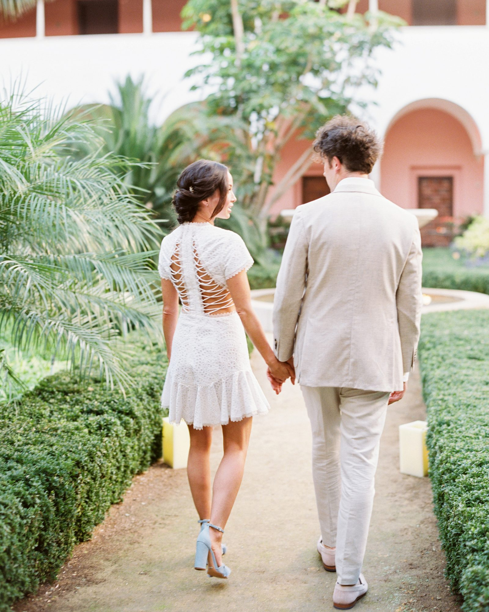 bride and groom holding hands walking down path