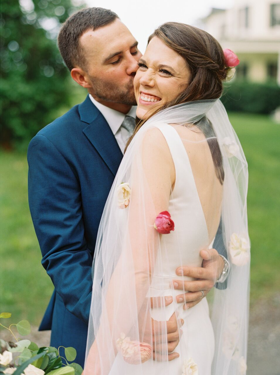 groom kissing bride flower veil