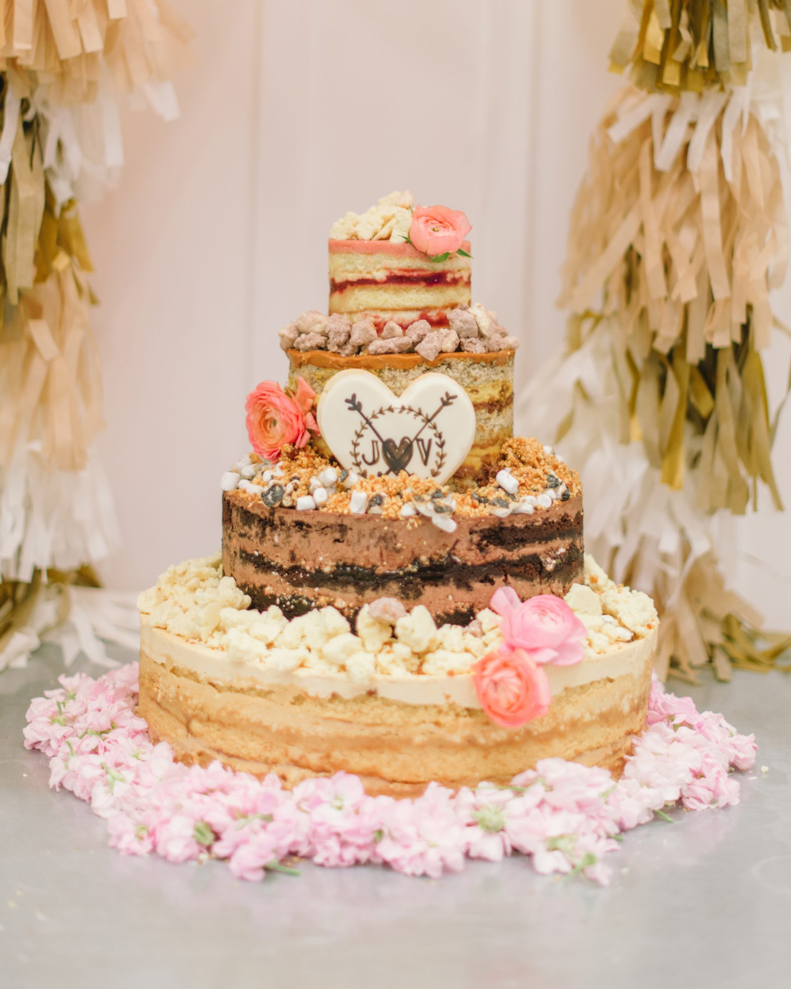 The new Mr. and Mrs. cut into this four-tier wedding cake from Momofuku Milk Bar at this California wedding. They kept the strawberry lemon-flavored top tier for their first anniversary.