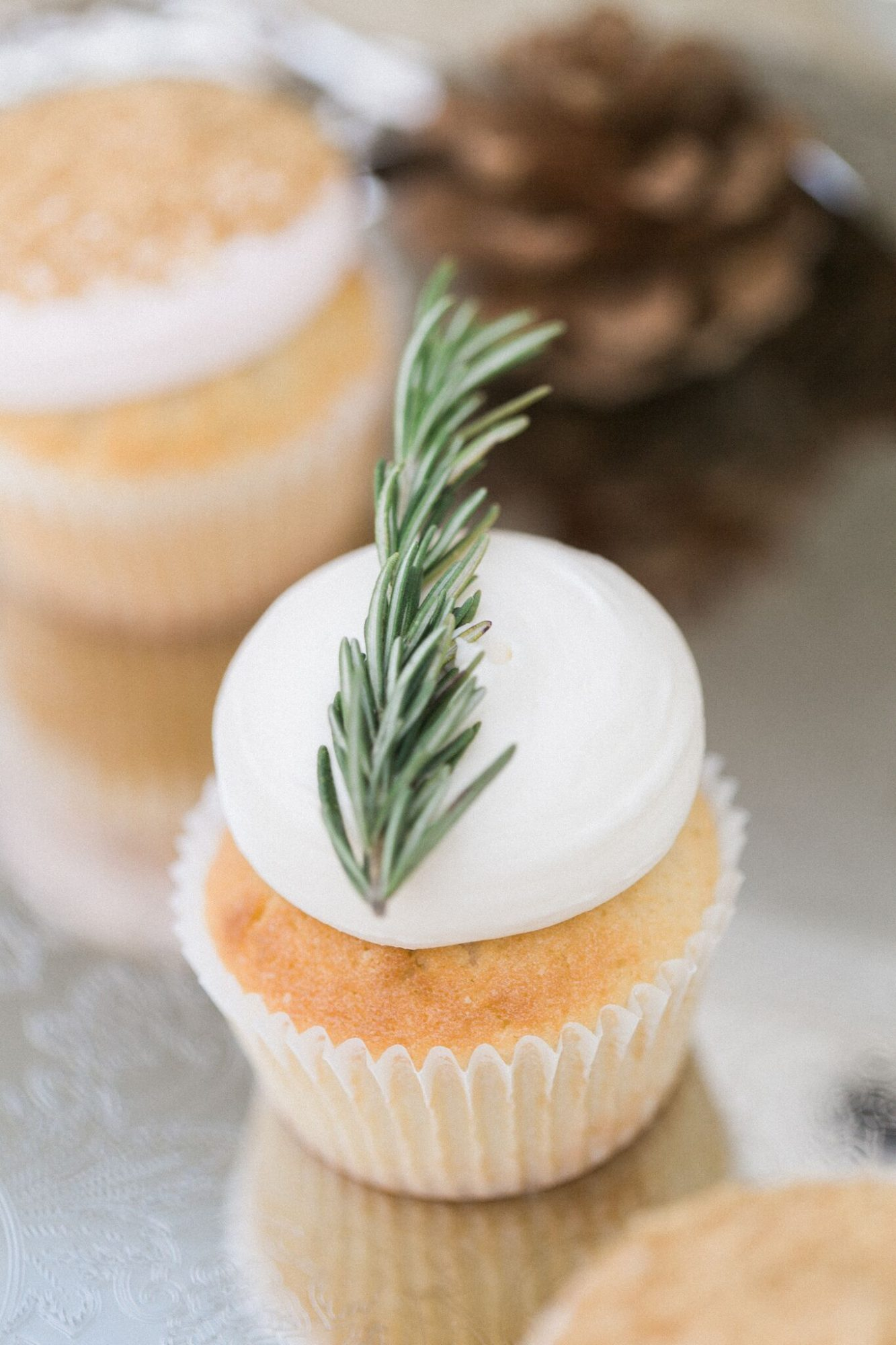 vanilla cupcake with frosting and rosemary sprig