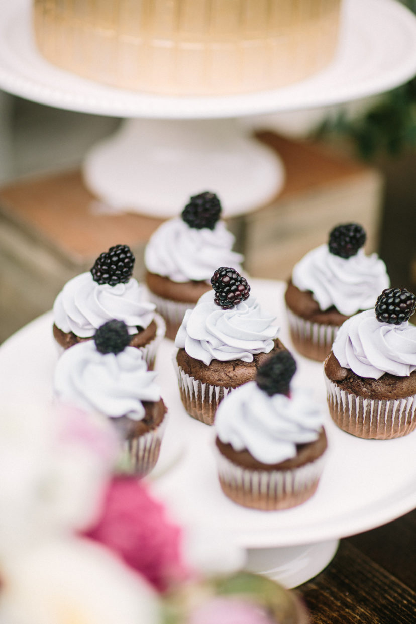 chocolate cupcakes with white frosting and black berries