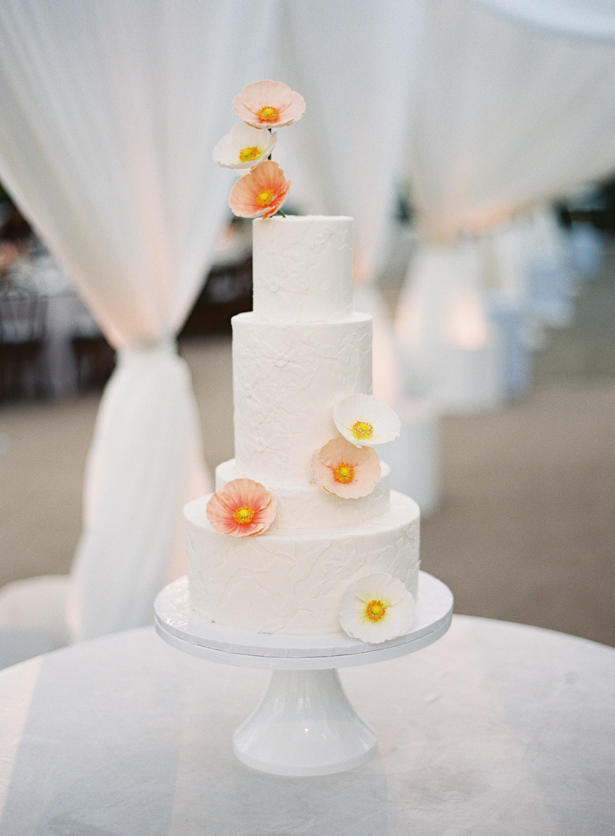 white textured cake with poppy flowers