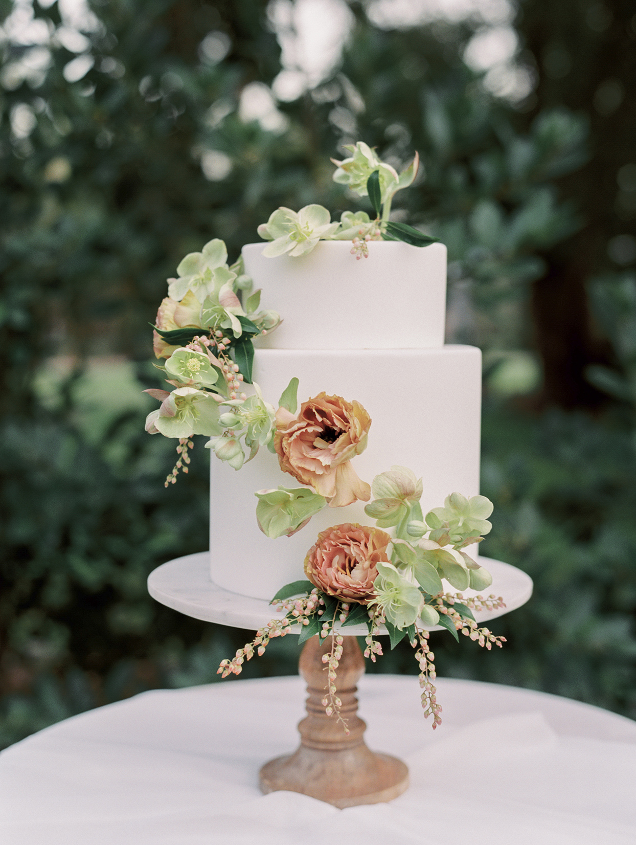 white wedding cake with sash of flowers and buds