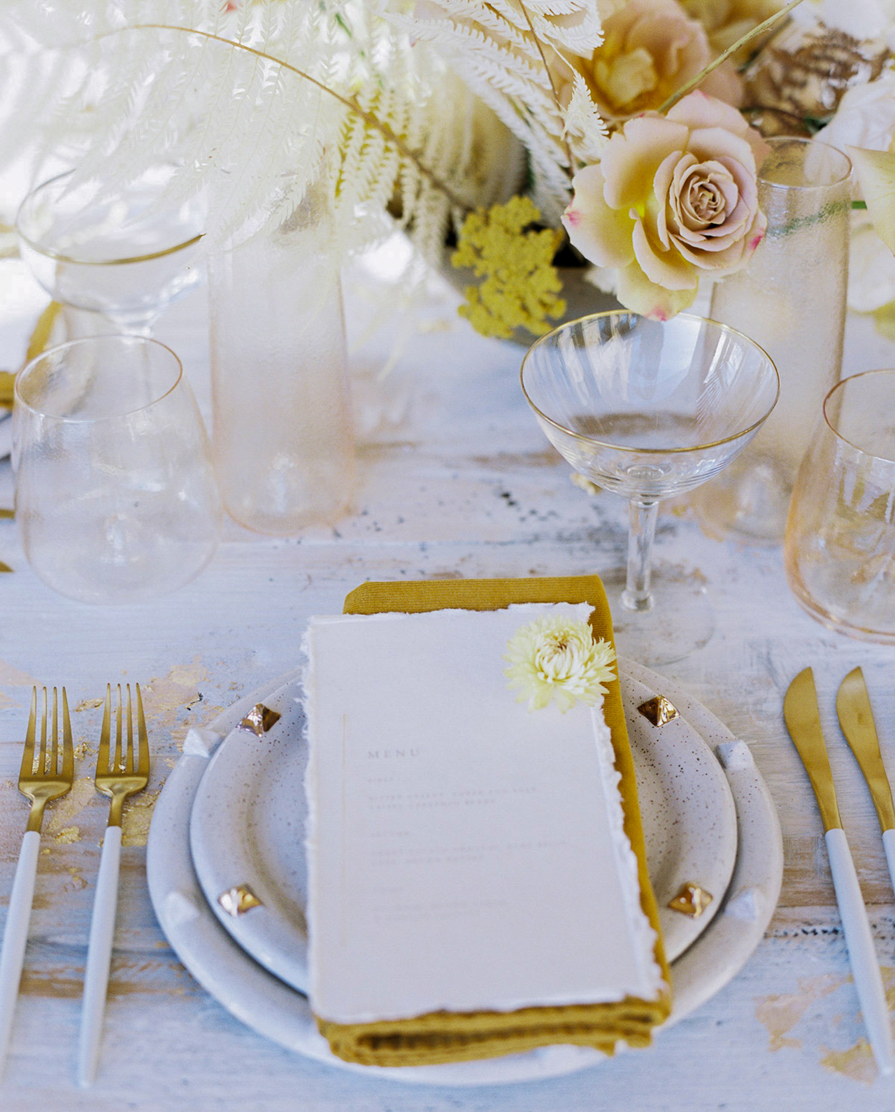 Brass-studded plates mustard linens white-coated gold flatware