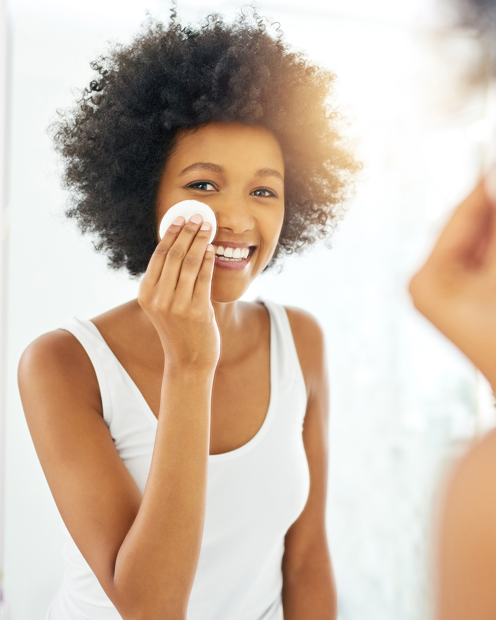 woman applying face product with cotton round