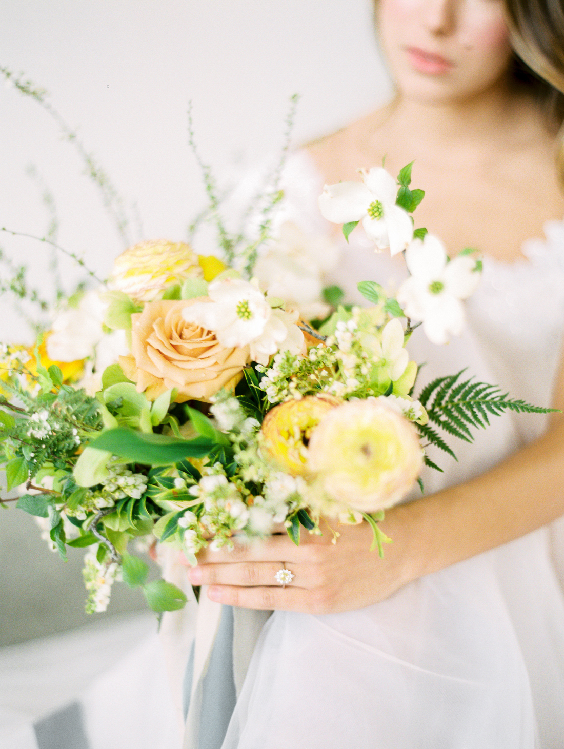 bouquet of light orange roses, greenery, and yellow blooms