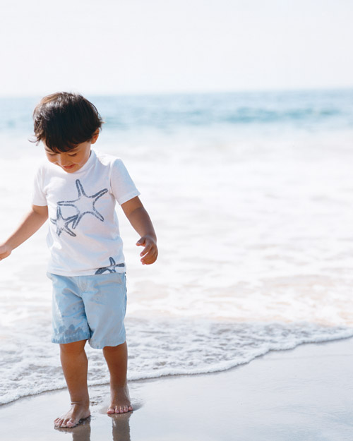 boy walking on beach wearing shell t-shirt