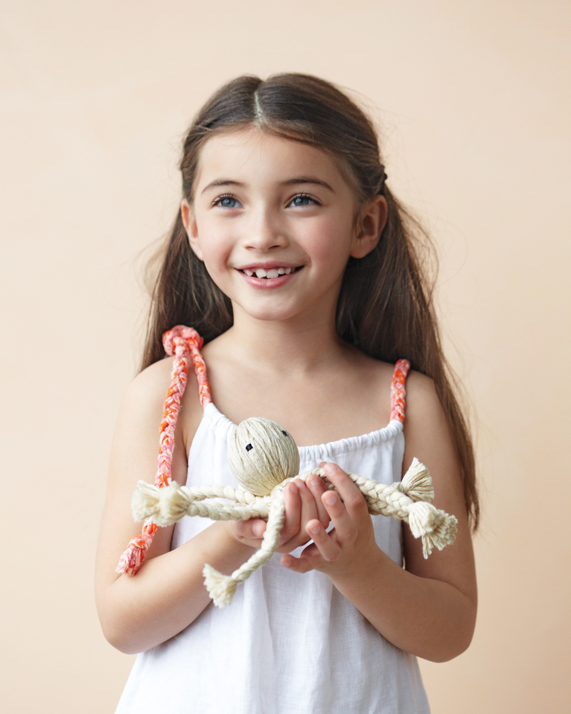 kid holding braided octopus doll