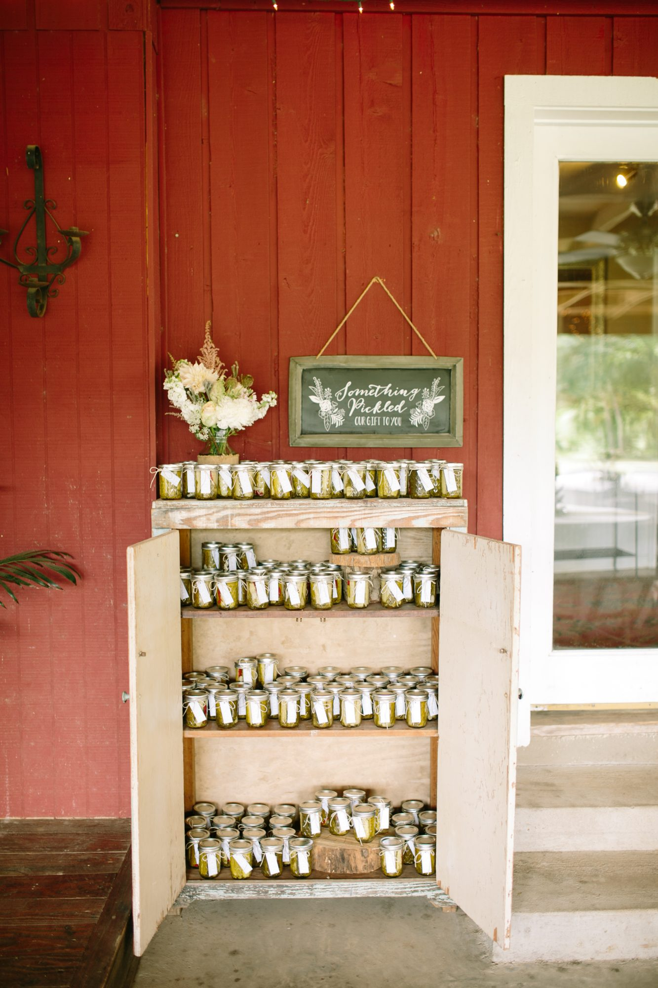 Draw guests' attention to your favors with a sign that references the treats themselves, like this vintage-styled option that showcased the couple's jarred pickle take-homes.