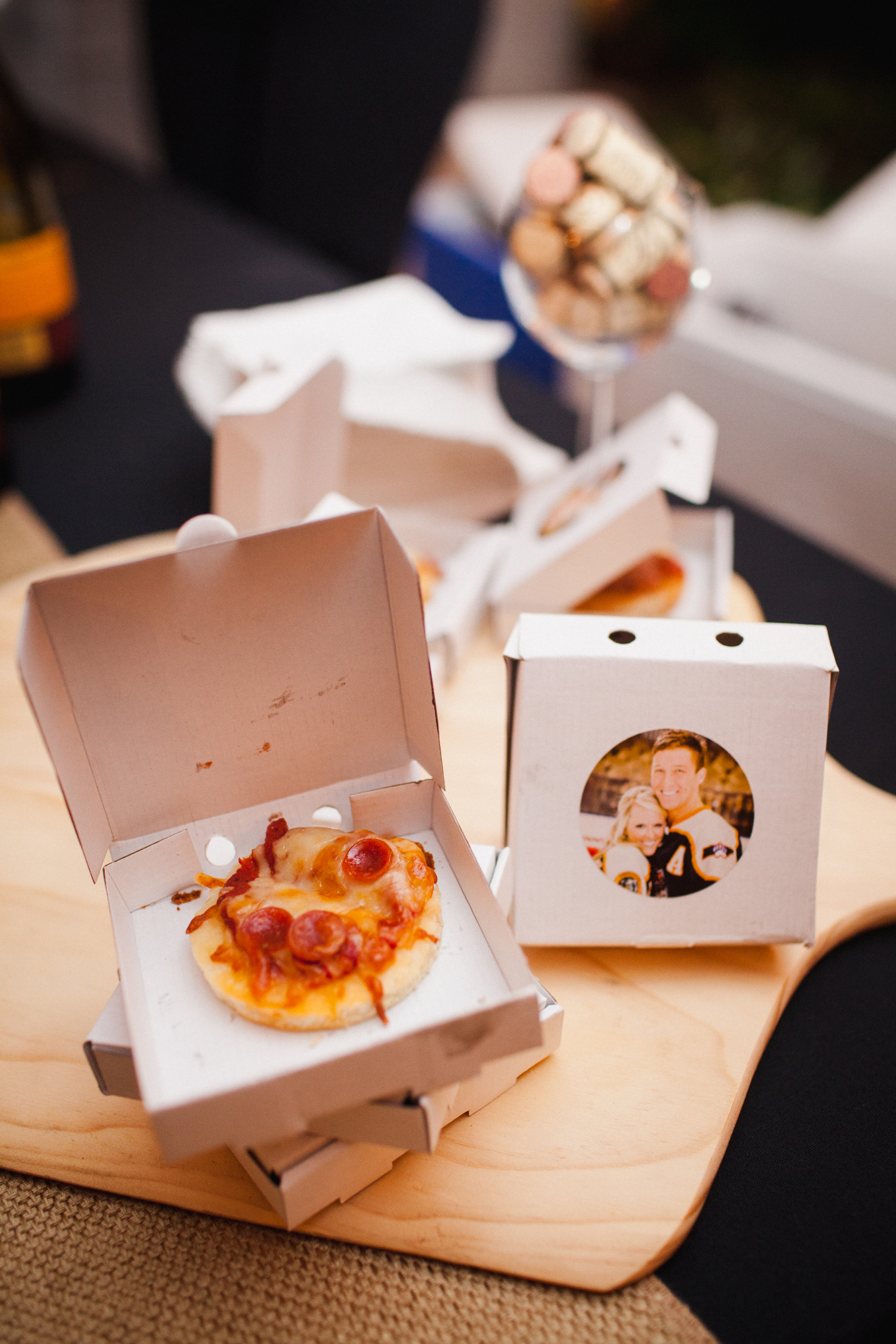 Serving pizza bites in mini pizza boxes that feature your faces on them, like these created by Bradford Catered Events, is a creative favor idea that will gain you major originality points.