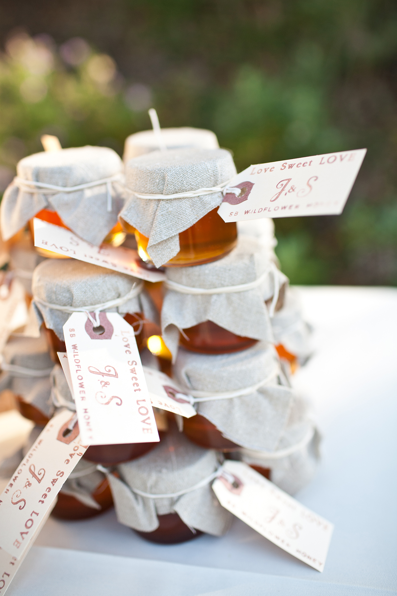 Dainty jars of honey, like these ones from Savanah Bee Company, can be topped with monogram-printed tags for a rustic wedding.
