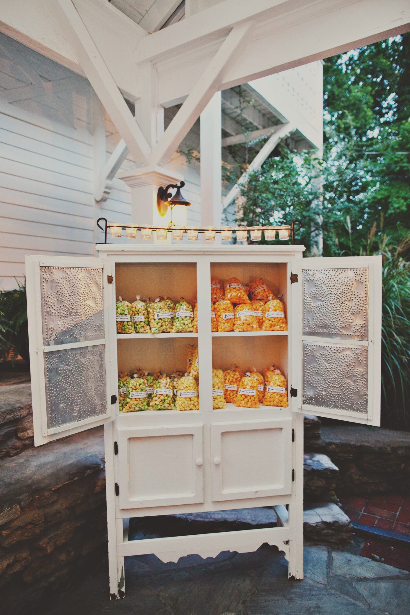 This rustic cabinet, full of a plethora of popcorn types, proves that wedding favors can serve as big-day décor, too.