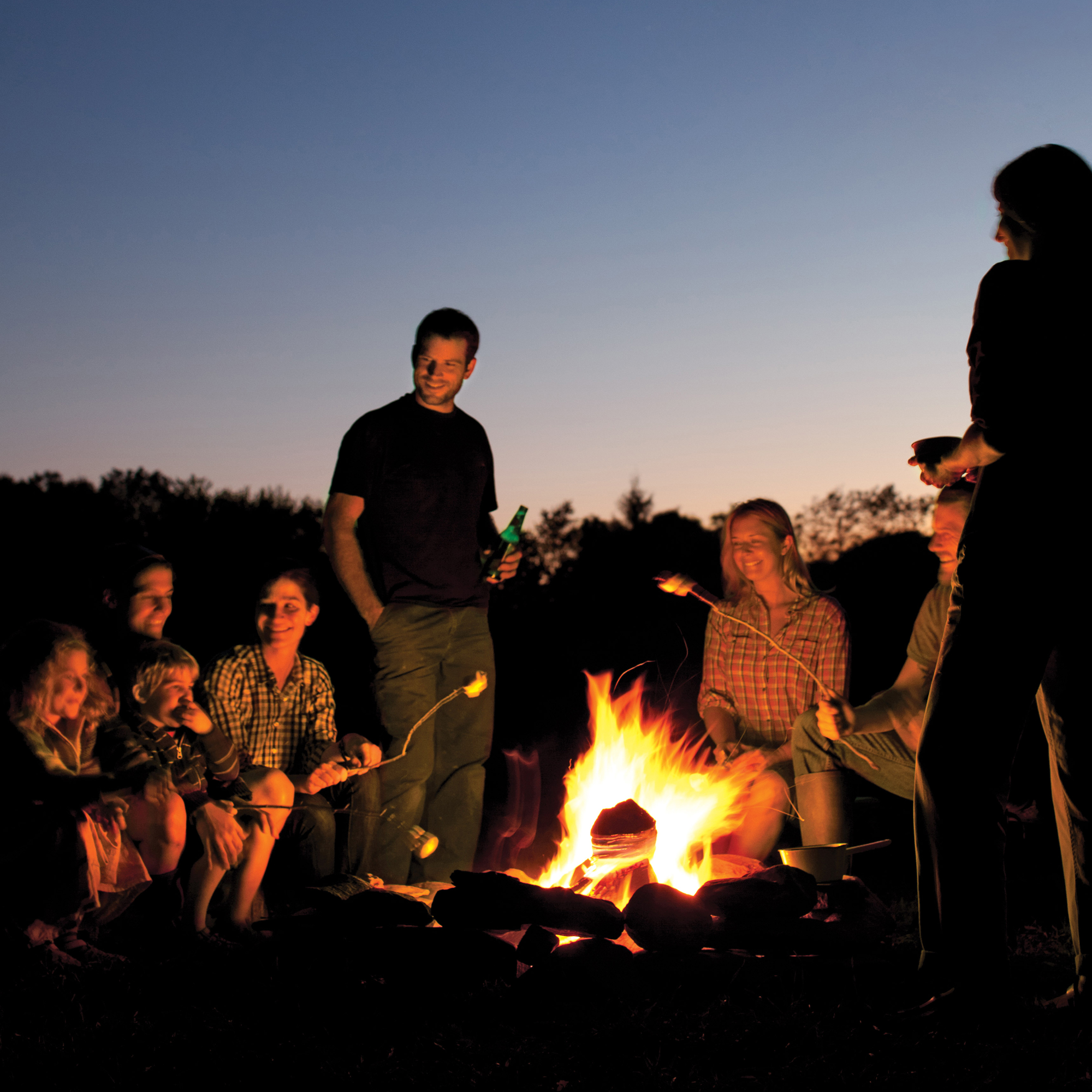 group of people sitting around campfire roasting marshmallows