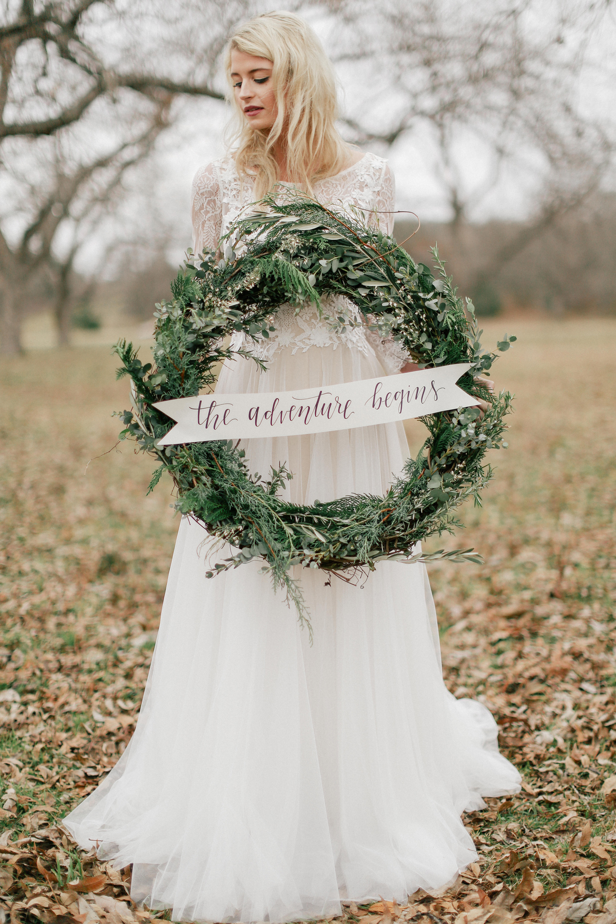 wedding wreath with sign held by bride