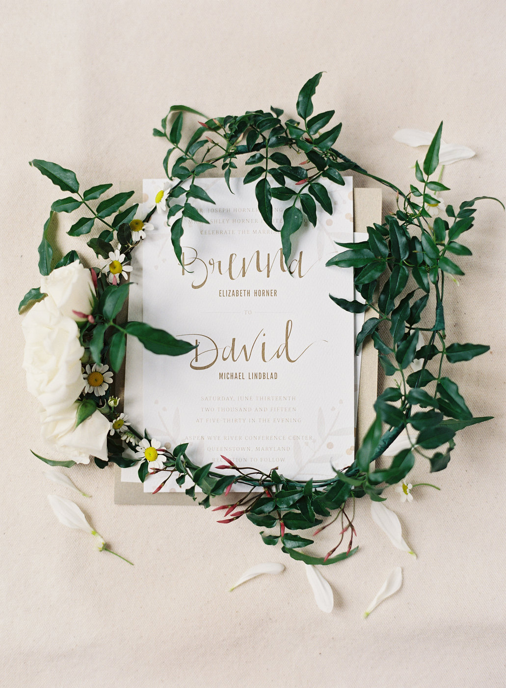 wedding wreath with daisies displayed on top of stationary suite