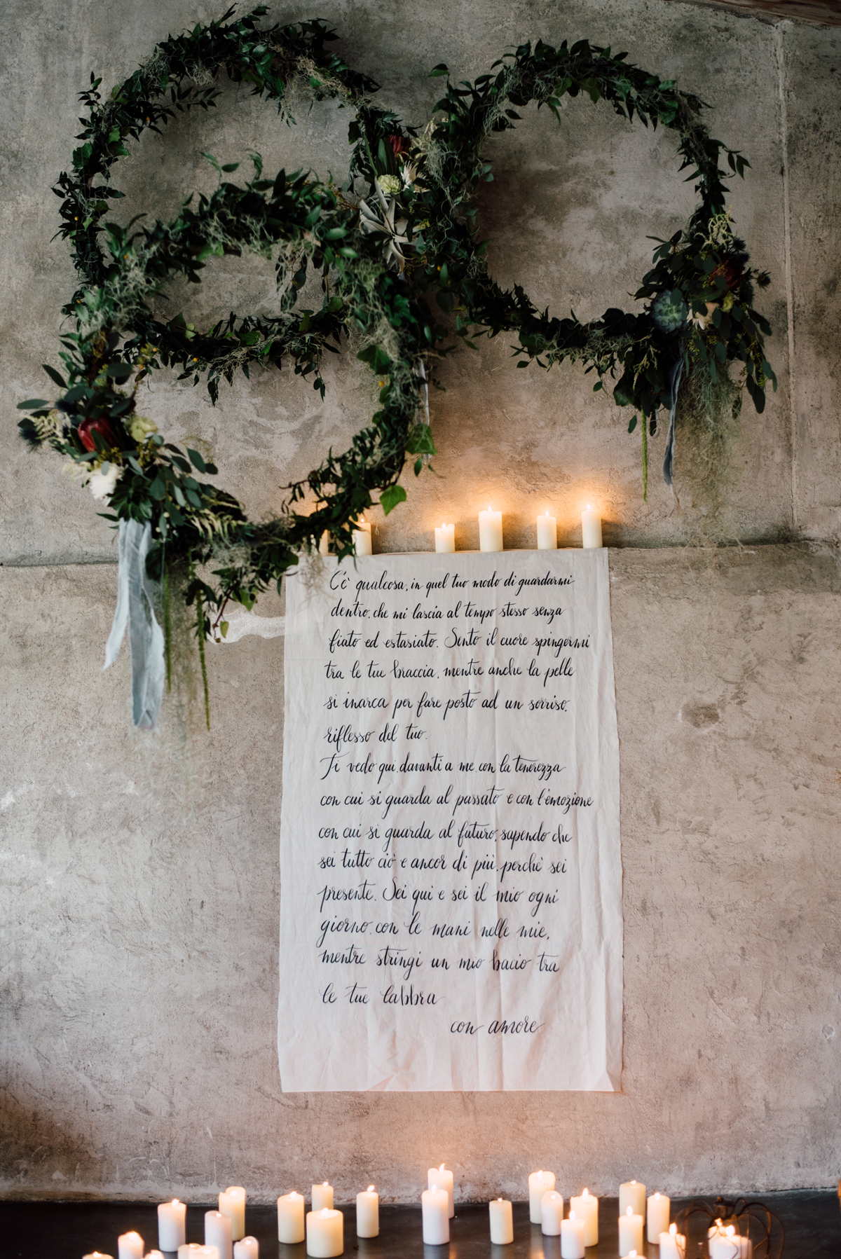 wedding wreaths hanging above quote on linen surrounded by candles