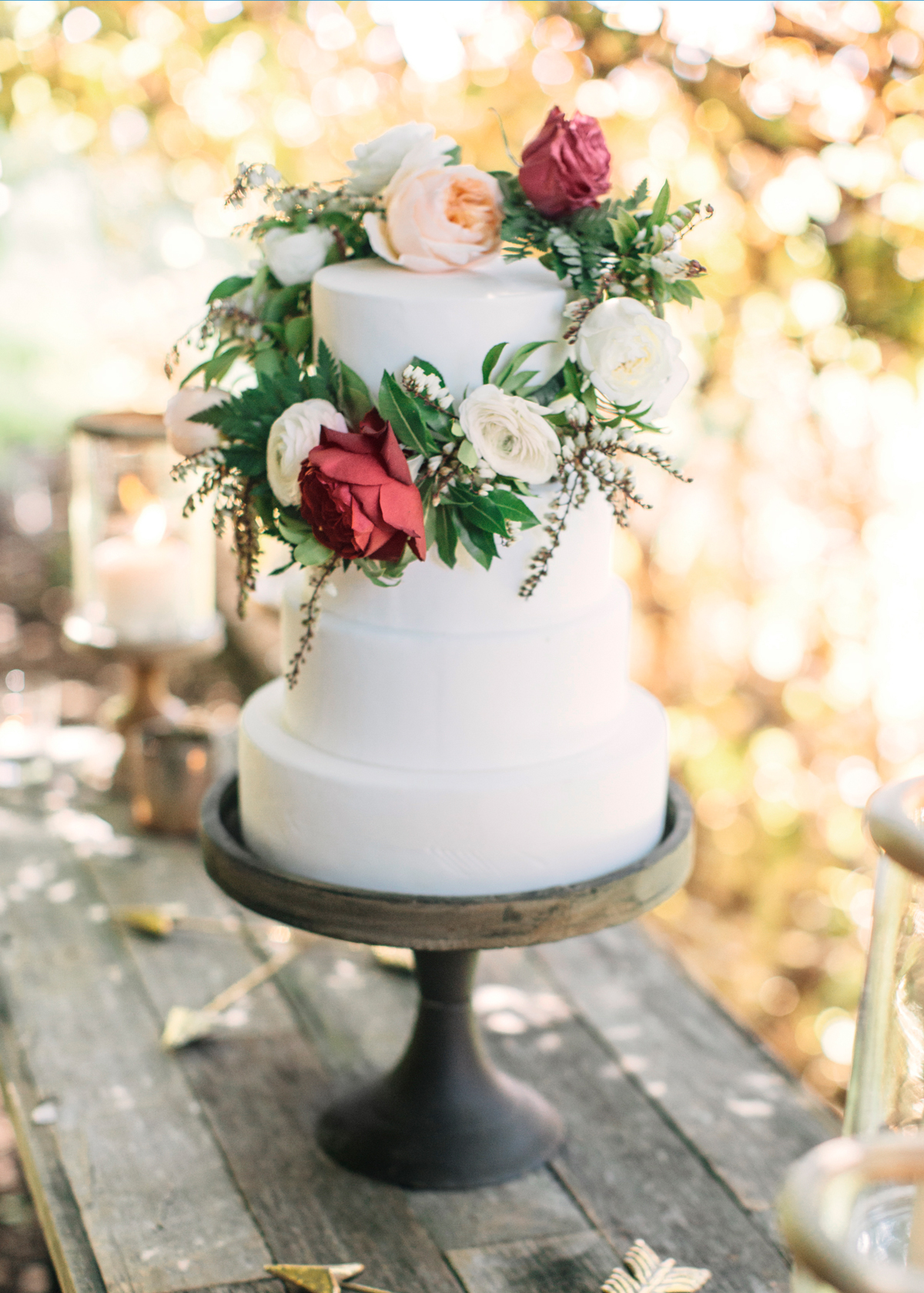 wedding wreath with roses decorating white wedding cake