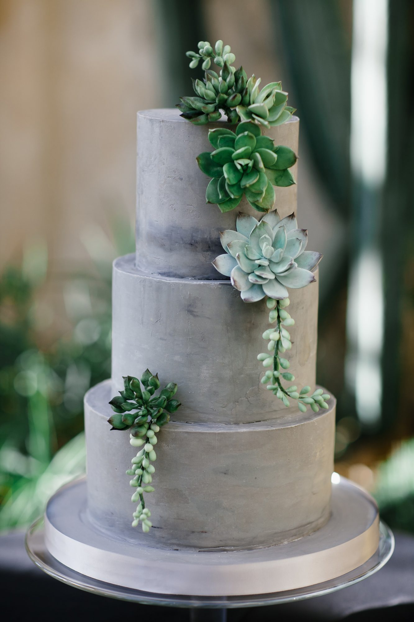 three tiered gray frosted wedding cake with succulent decor