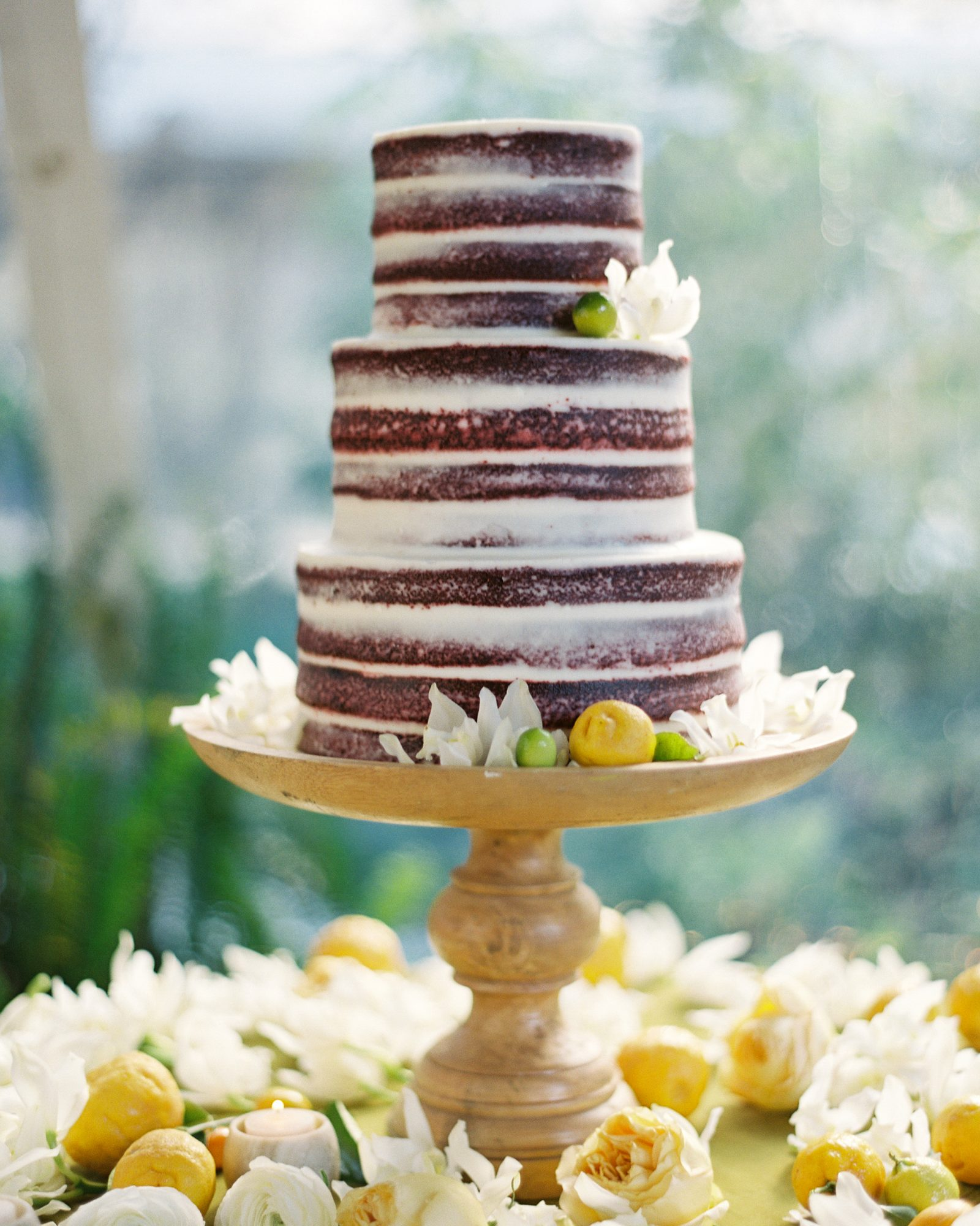 The naked wedding cake: It's a trend that's clearly here to stay, as couples and their bakers are forgoing an outer layer of icing in favor of an unfrosted confection that looks just as good as it tastes. If you're not a fan of the traditional three-tiered white wedding cake, this big-day dessert alternative might just be for you.                                       As these naked wedding cake ideas will show, there's a style for every celebration, whether you're after a naked rustic wedding cake or a modern one featuring unexpected flavors.  Naked wedding cakes aren't all about looks and taste, though. There's actually a serious benefit to choosing an unfrosted confection, and that's freshness.                                       Because frosting locks in moisture, a baker is able to whip up a traditional wedding cake in advance of the big day, then add the finishing touches right before delivery. That's not the case with an exposed wedding cake, which needs to be baked relatively close in time to the reception to ensure each layer is fresh, moist, and delicious. That means your pro will likely pop your tiers into the oven the night before or even the day of your nuptials. Nothing beats a cake baked just hours before it's eaten, right?                                        Whatever your reason for choosing one, you'll soon see that bare wedding cakes can be chic, sophisticated, and beautiful—not too sweet, but just sweet enough. Click through to see some of our favorite examples, starting with this stunning half-dressed wedding cake (topped with lemons and limes) by Lelé Pâtisserie.
