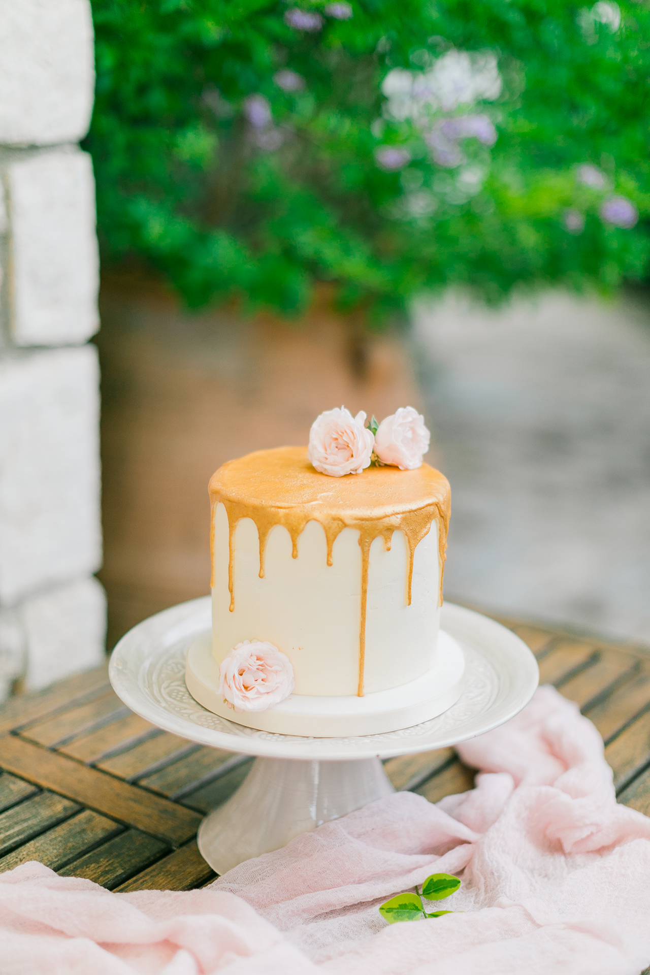 one tier dessert cake with gilded drips and flowers