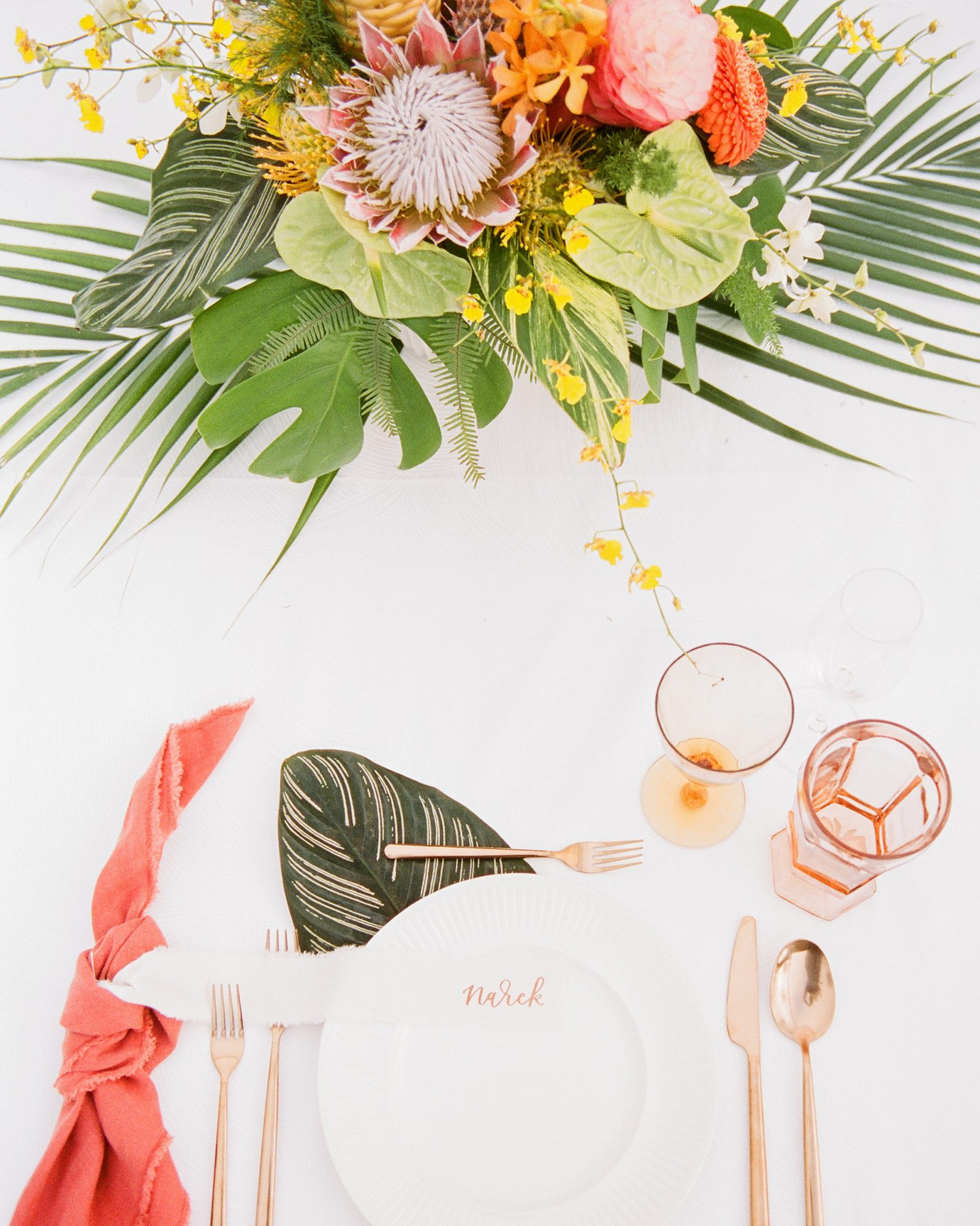 tropical wedding centerpiece filled with protea, monstera, and palm leaves and greenery underneath salad plates