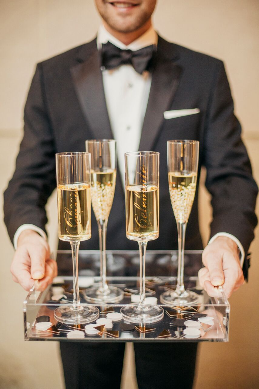 """At this wedding, Champagne was served infun glassware. Confetti and words like """"Cheers"""" and """"Celebrate"""" adorned each flute."""
