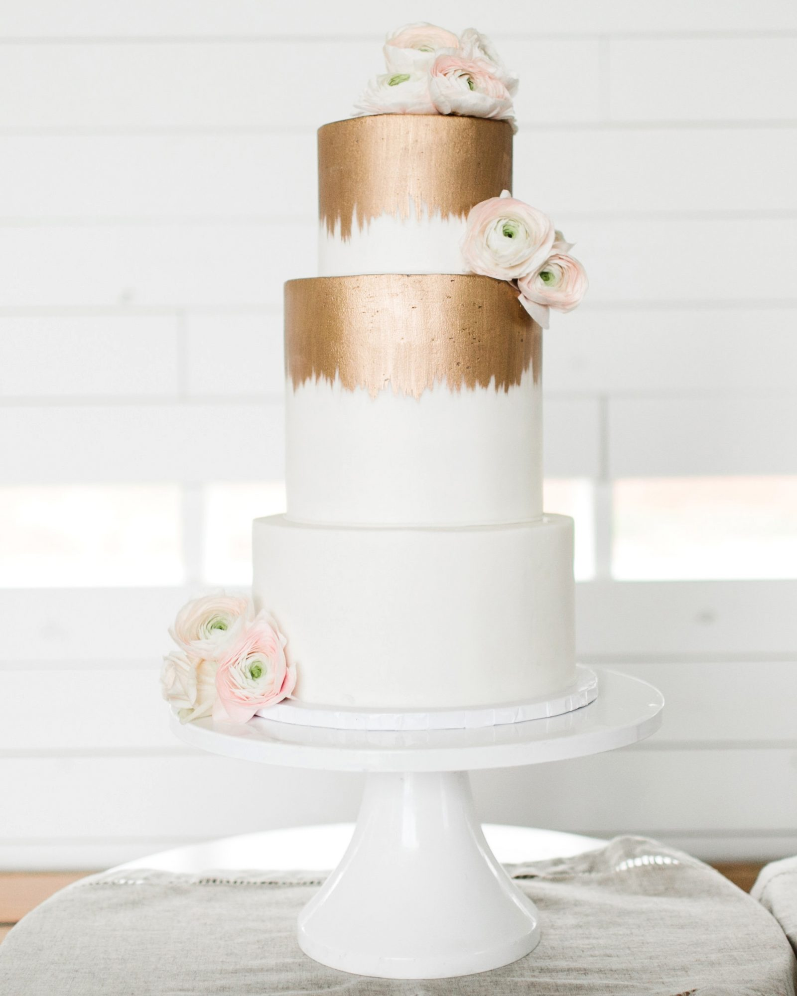 The cake, by Sweet Treats Bakery in Austin, was a white-chocolate flavored confection with raspberry filling. It was gilded in bronze—matching the metallic-and-white color scheme—with a few ranunculus on each tier.