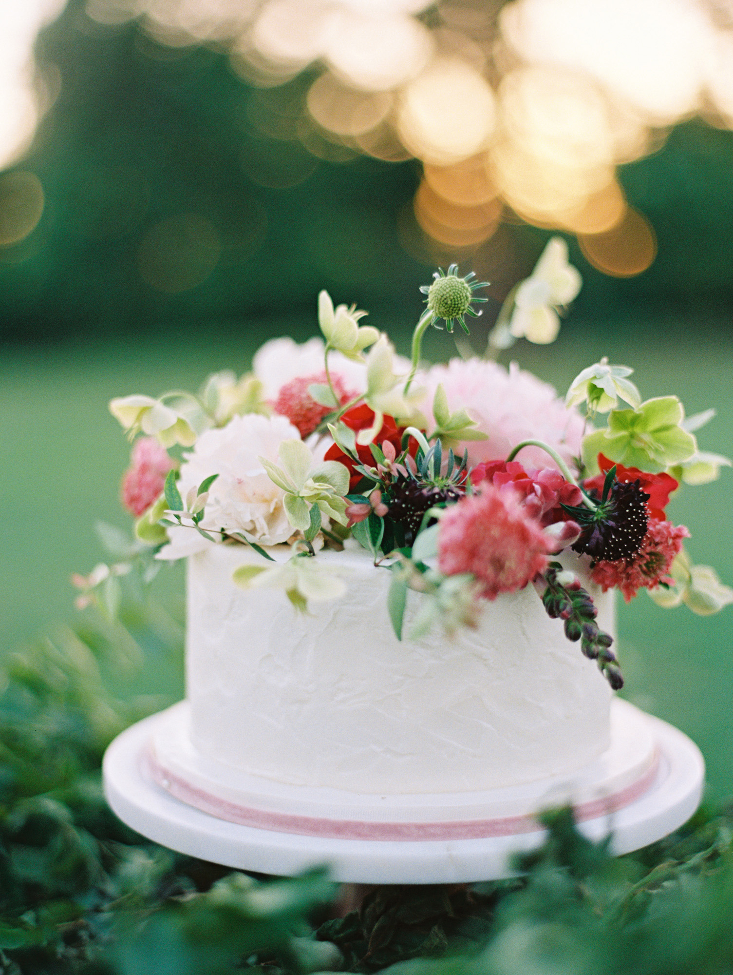 The two smaller single-tier cakes, also by Amy Cakes, were simply iced and topped with fresh blooms.