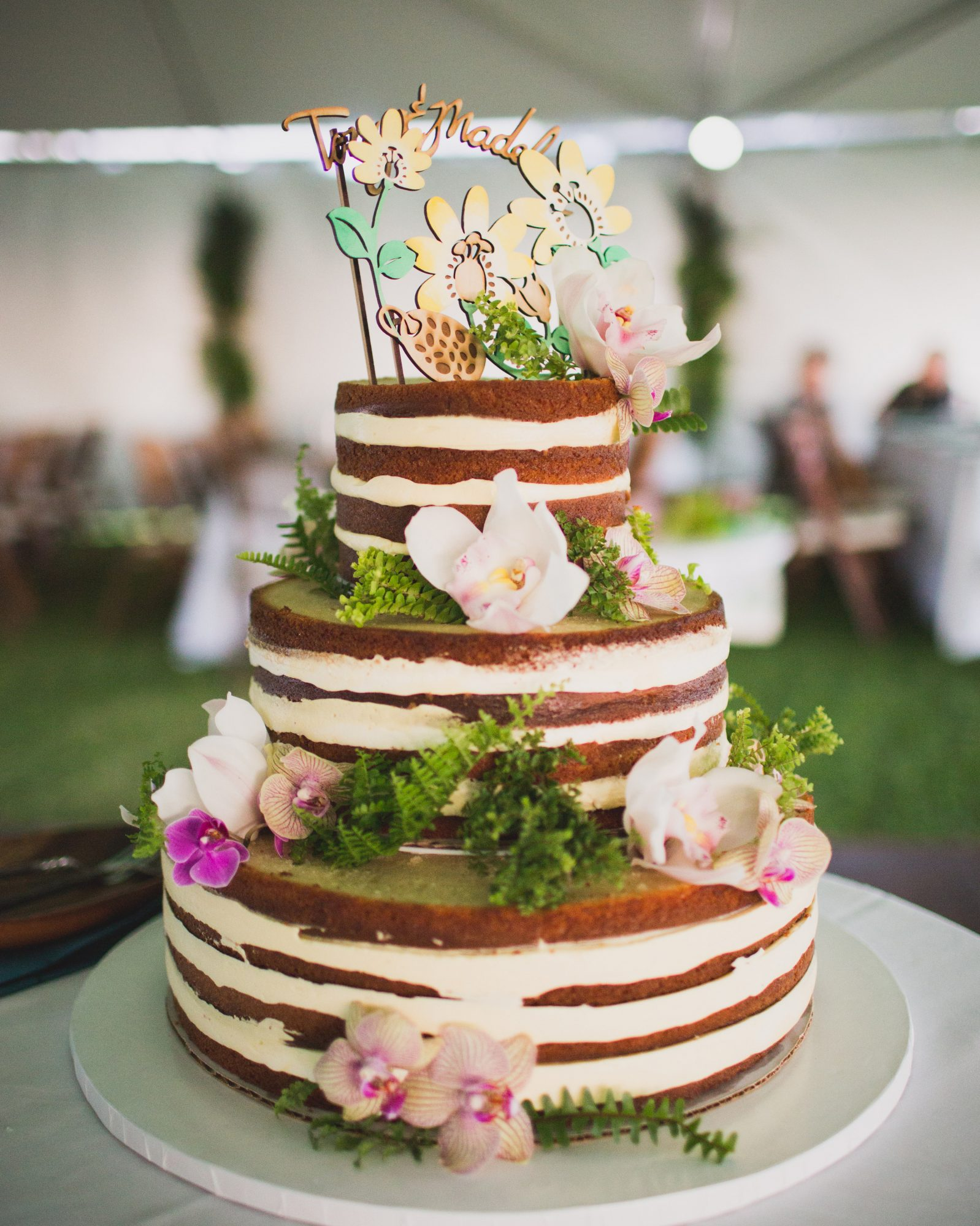 The passionfruit-soaked white cake, made by Celebrations Maui, at this Hawaii wedding was adorned with island blooms and a custom topper.