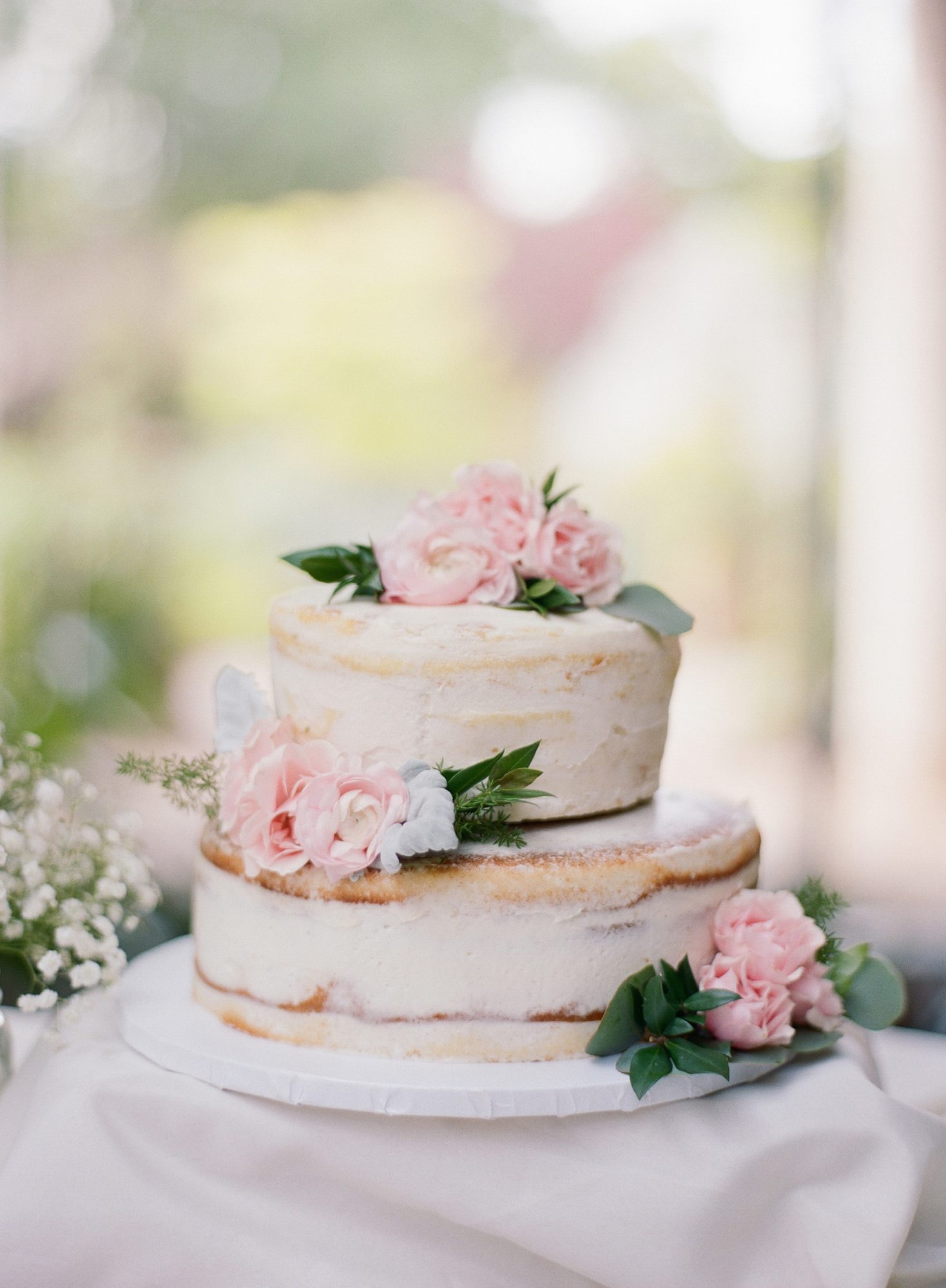 Pink flowers were used to spruce up this wedding cake. It was coated with just a bit of icing.