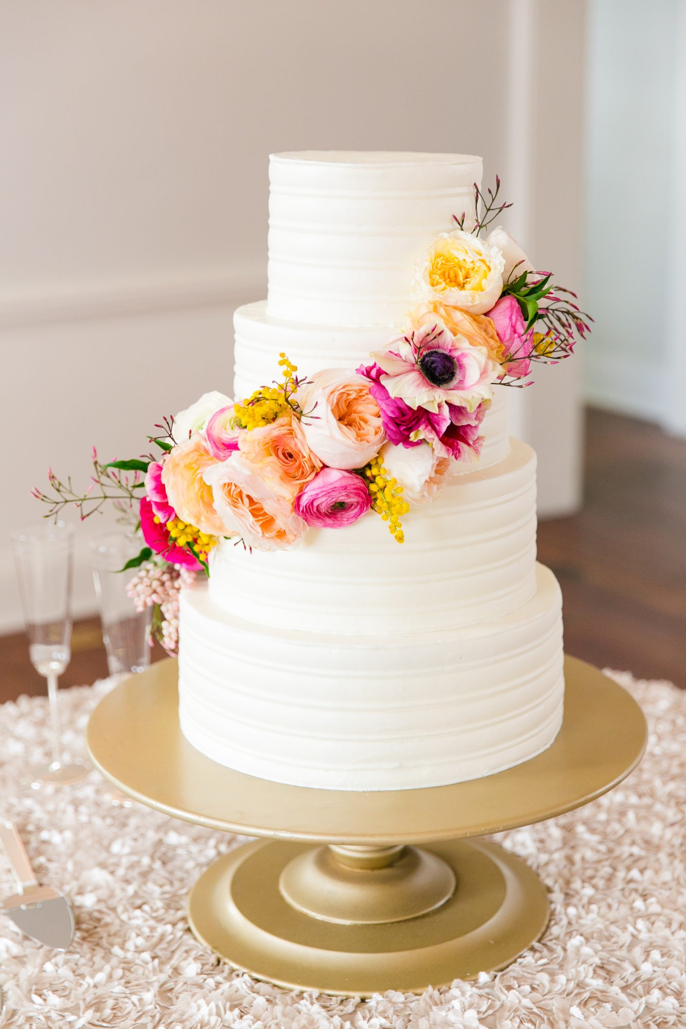 Pastels may be popular for spring weddings, but you can definitely opt for brighter shades, instead. This couple chose saturated pink and orange blooms for their cake.
