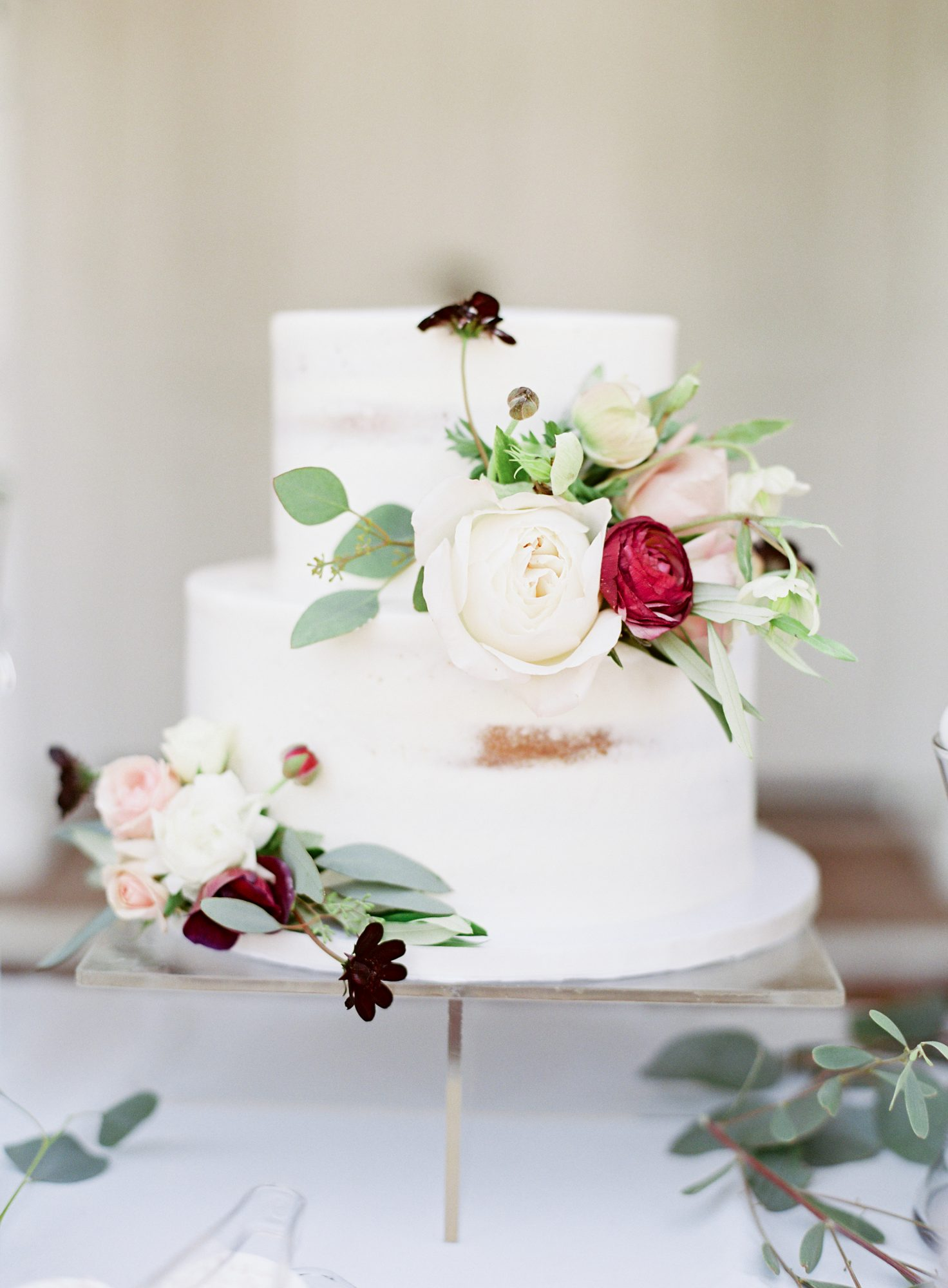 Little groupings of white, pink, red, and purple flowers decorated this sparsely-iced cake.