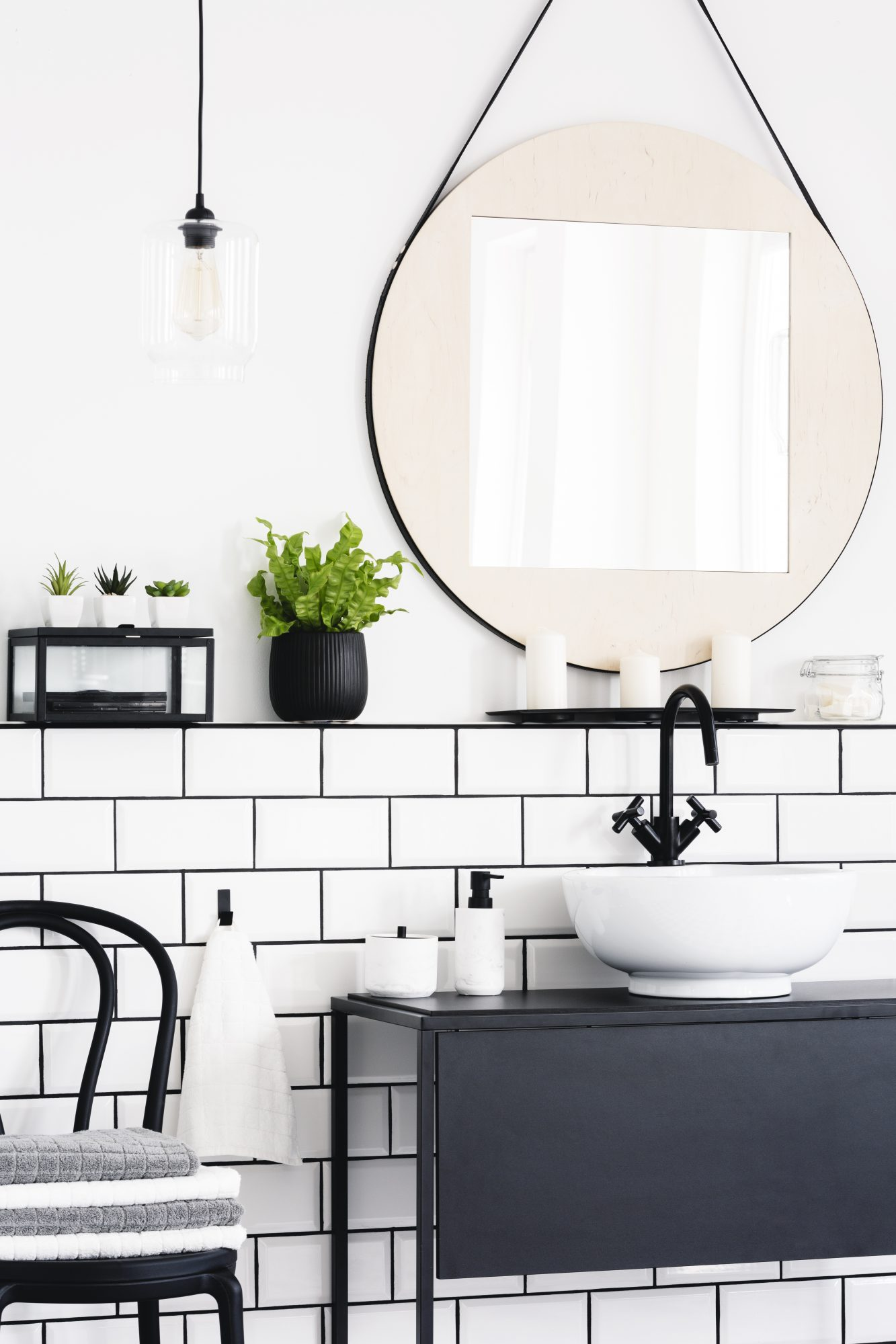 toilet interior with a mirror, plant, chair and black cupboard