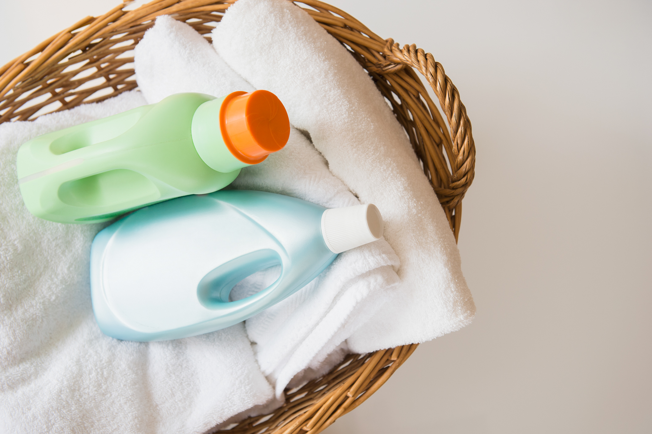 woven laundry basket with detergent and towels