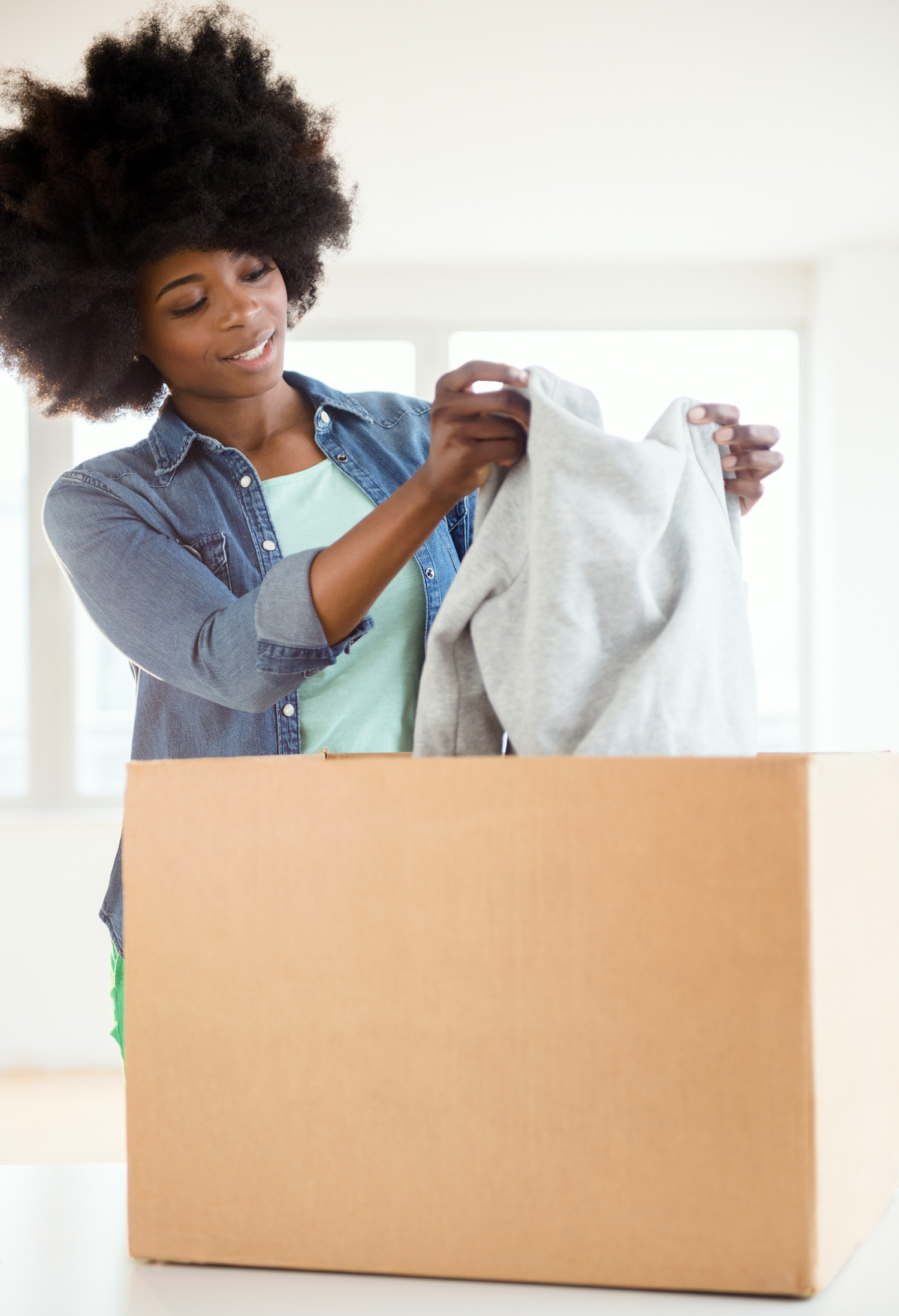 woman packing sweater in cardboard box