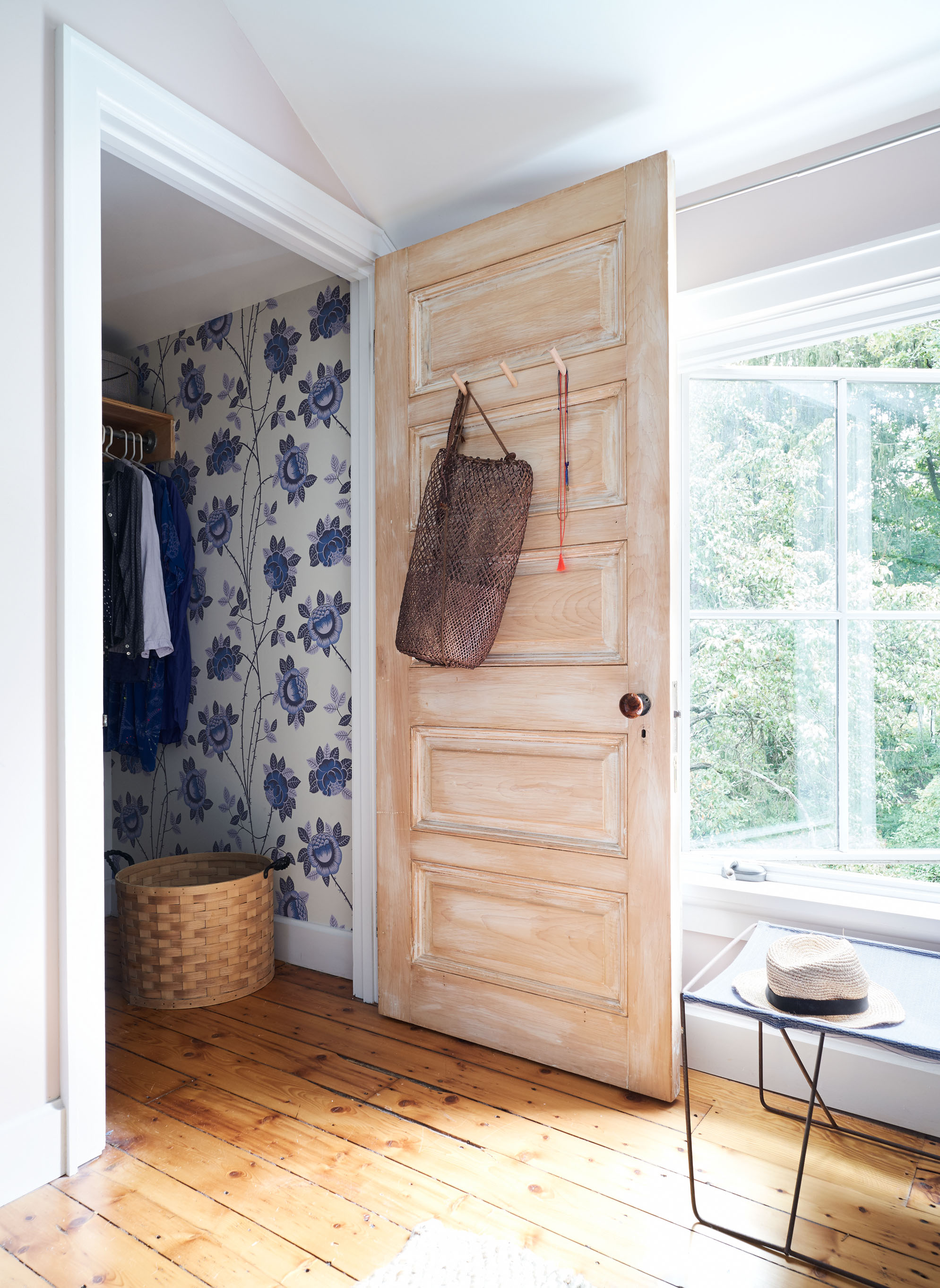 bedroom closet with refurbished door and blue floral wallpaper
