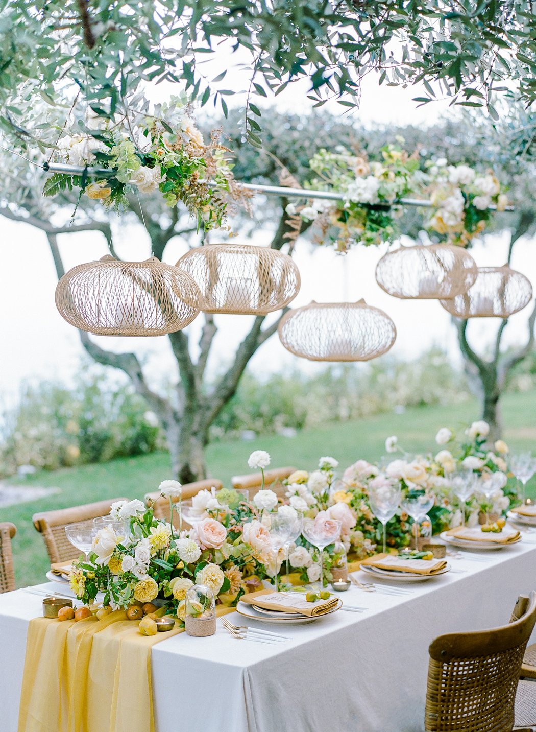 hanging lanterns over white and yellow reception tablescape