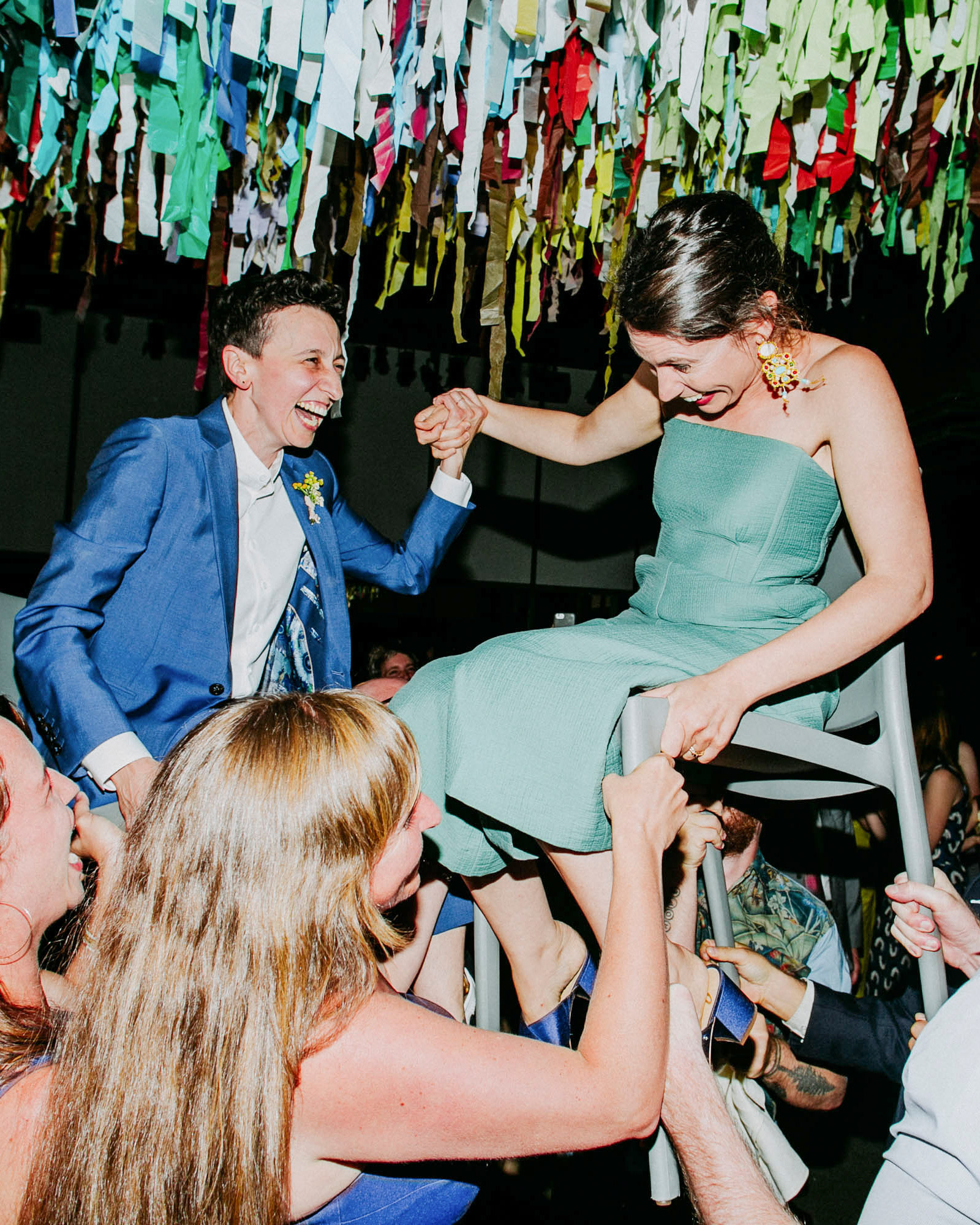 """Though the couple opted out of a first dance, Jenny and her dad took a spin on the dance floor to """"Highwayman"""" by Johnny Cash, Waylon Jennings, Willie Nelson, and Kris Kristofferson, a song that reminded her of her childhood. Then the brides were hoisted up in chairs as everyone did the hora. """"I'm Greek, so circle dancing is in our blood,"""" Maria says. """"It felt like a natural combination of our combined Greek and Jewish cultures."""""""