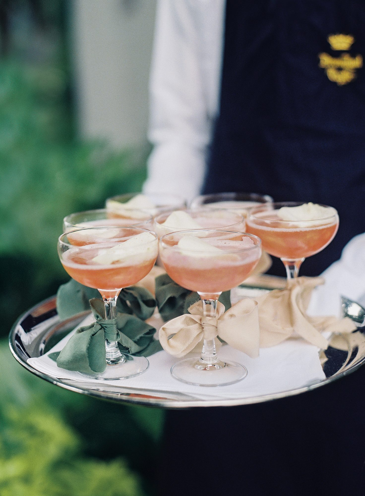 ribbon bows tied around glasses of rose on tray